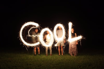 four people holding fireworks and forming cool word cool teams background