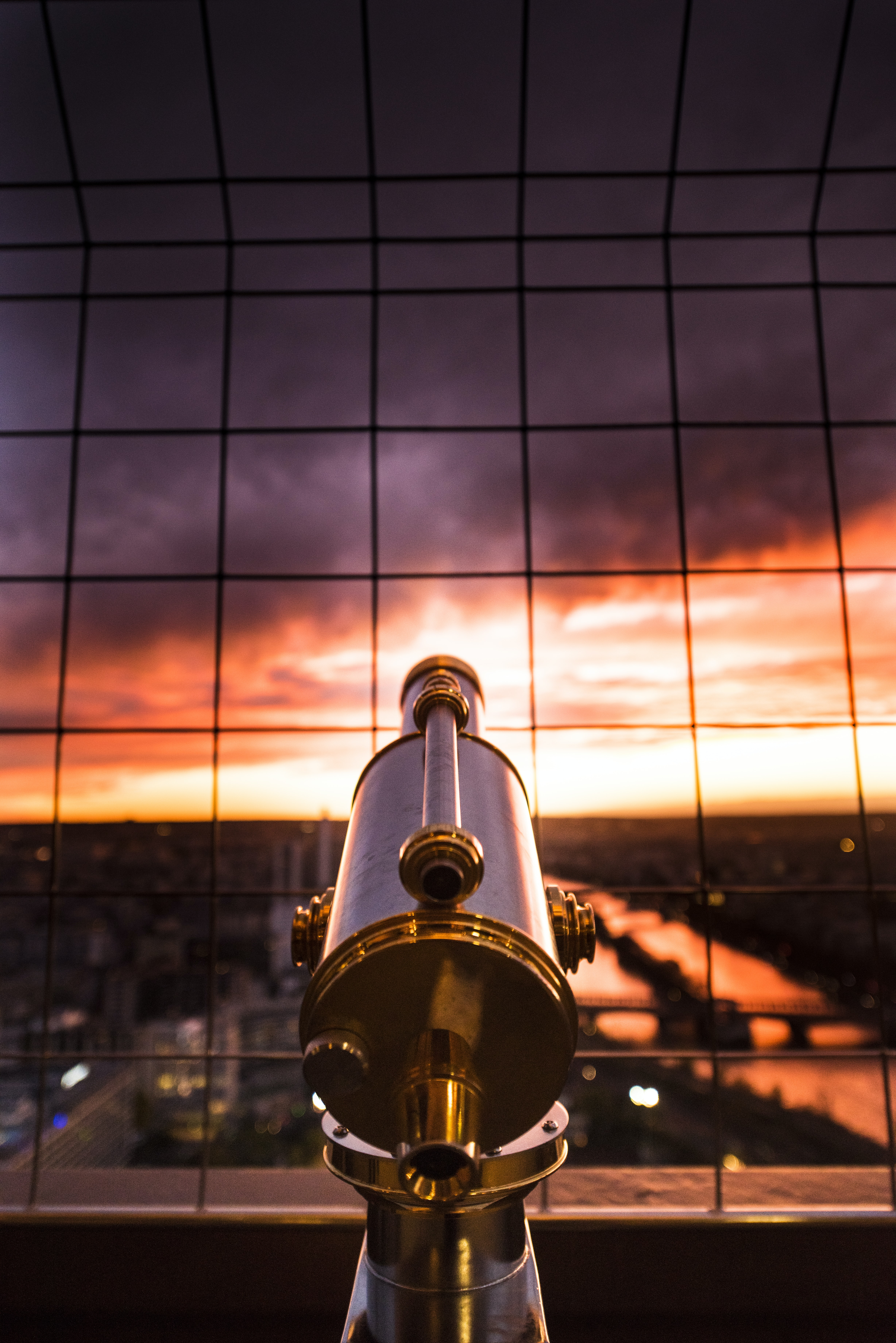 Looking at the sunset behind a telescope in Paris.