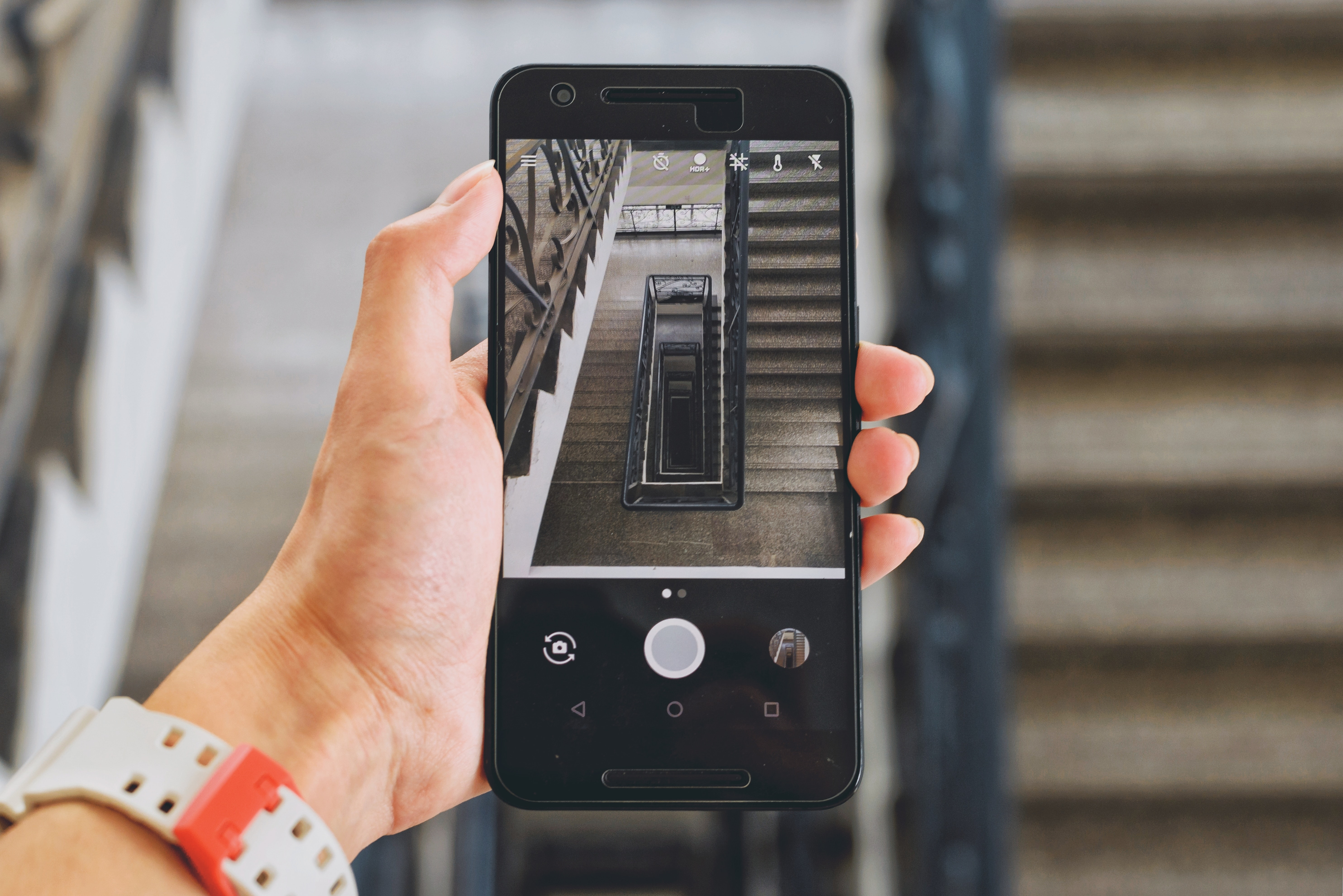 A person holding a smartphone with its camera pointed down a stairwell