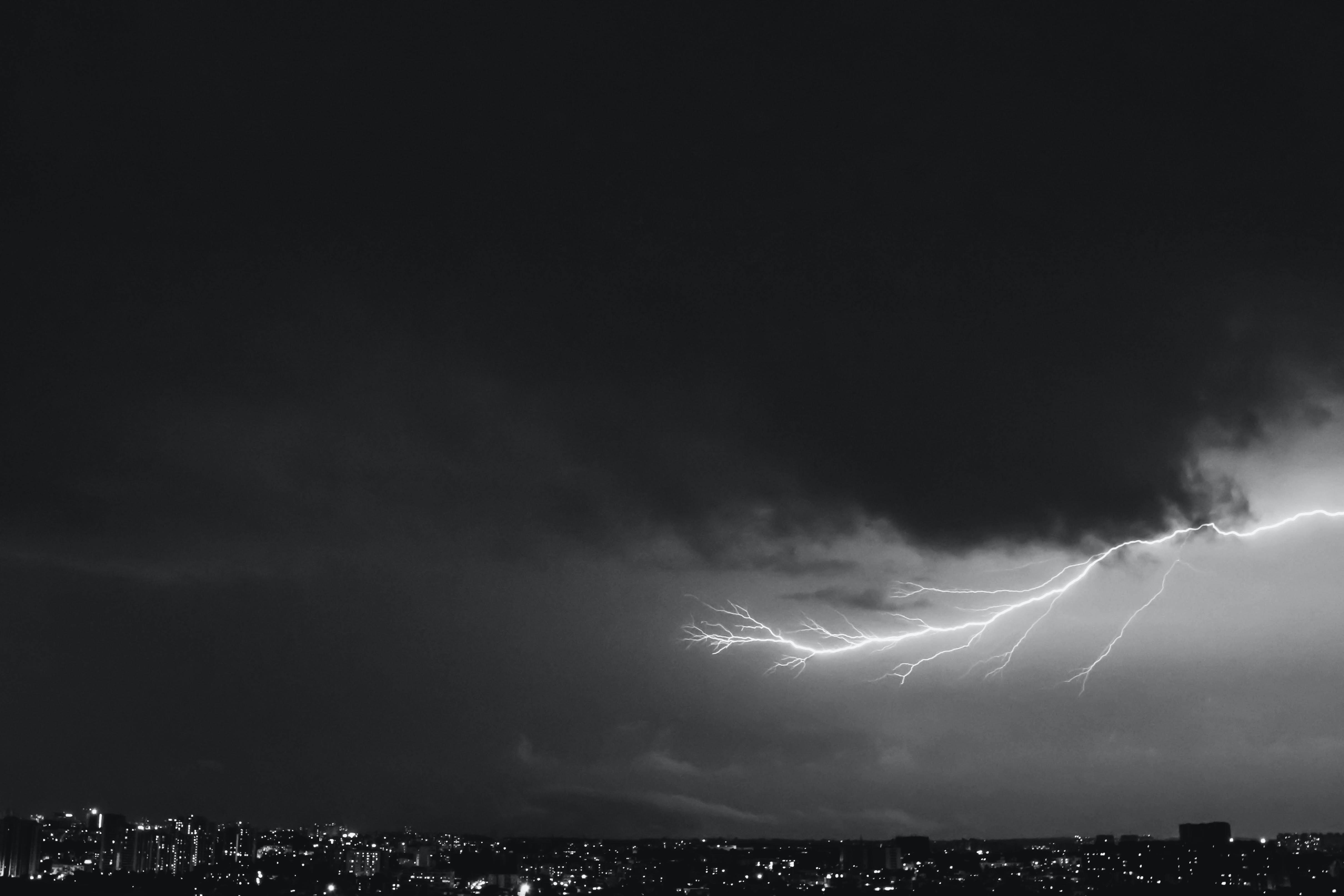 A long lightning bolt creeping across the night sky over a city