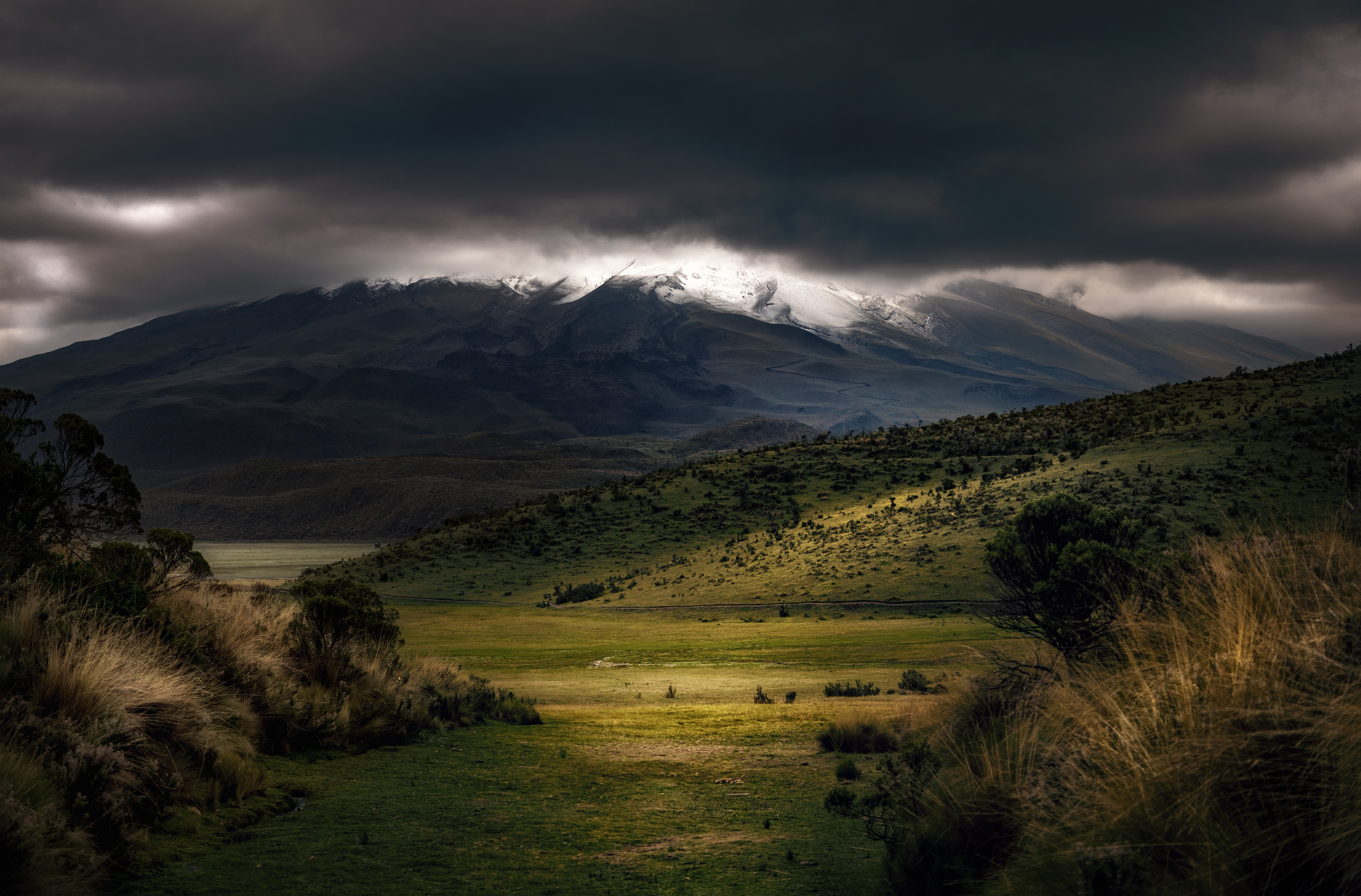 Gray clouds hover above green slopes as tall mountains emerge from the shadow on the horizon