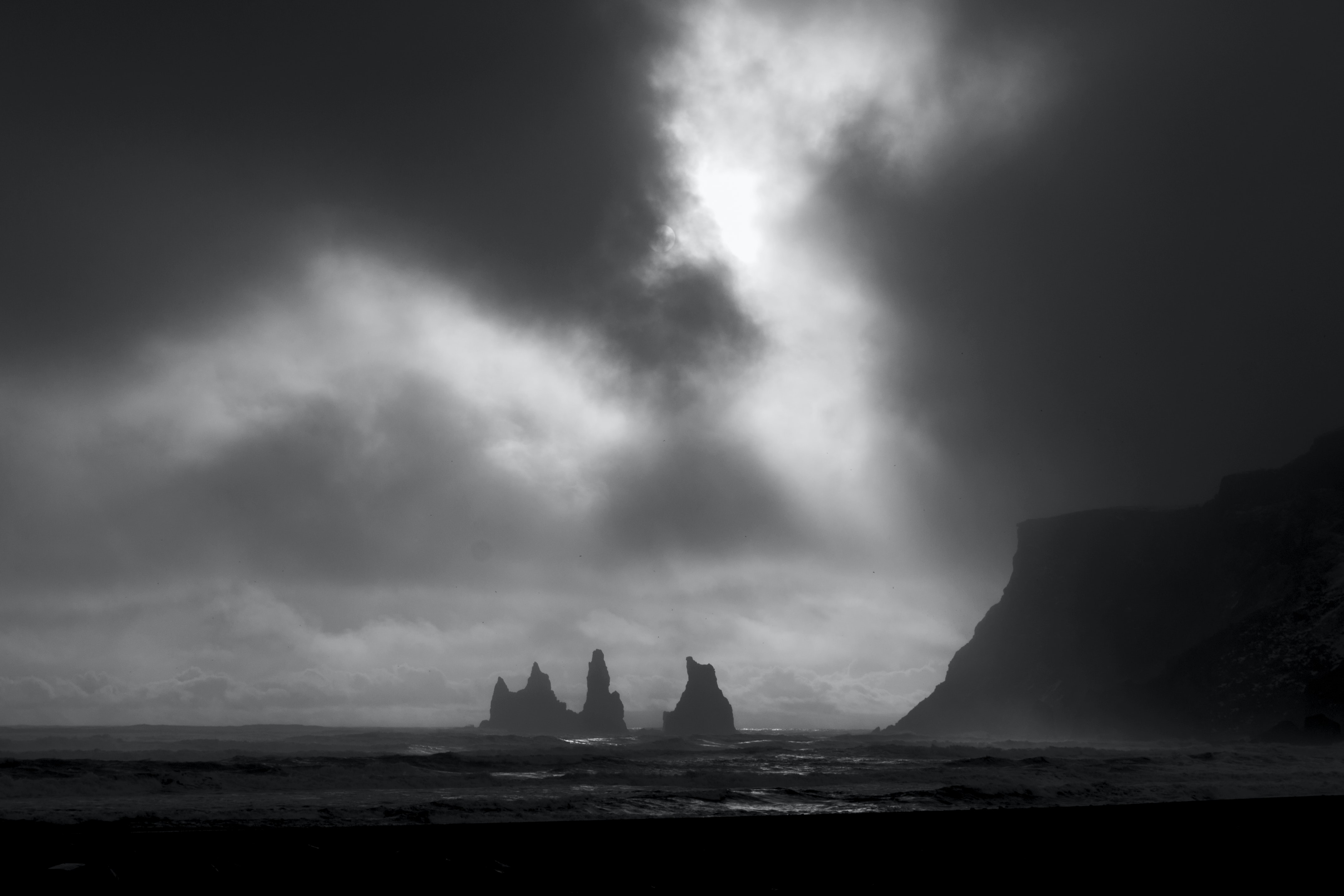 Dark sky over rock formations in a stormy sea
