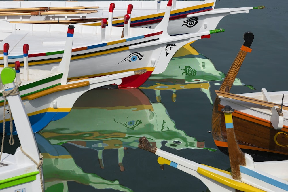 white wooden boats on body of water art