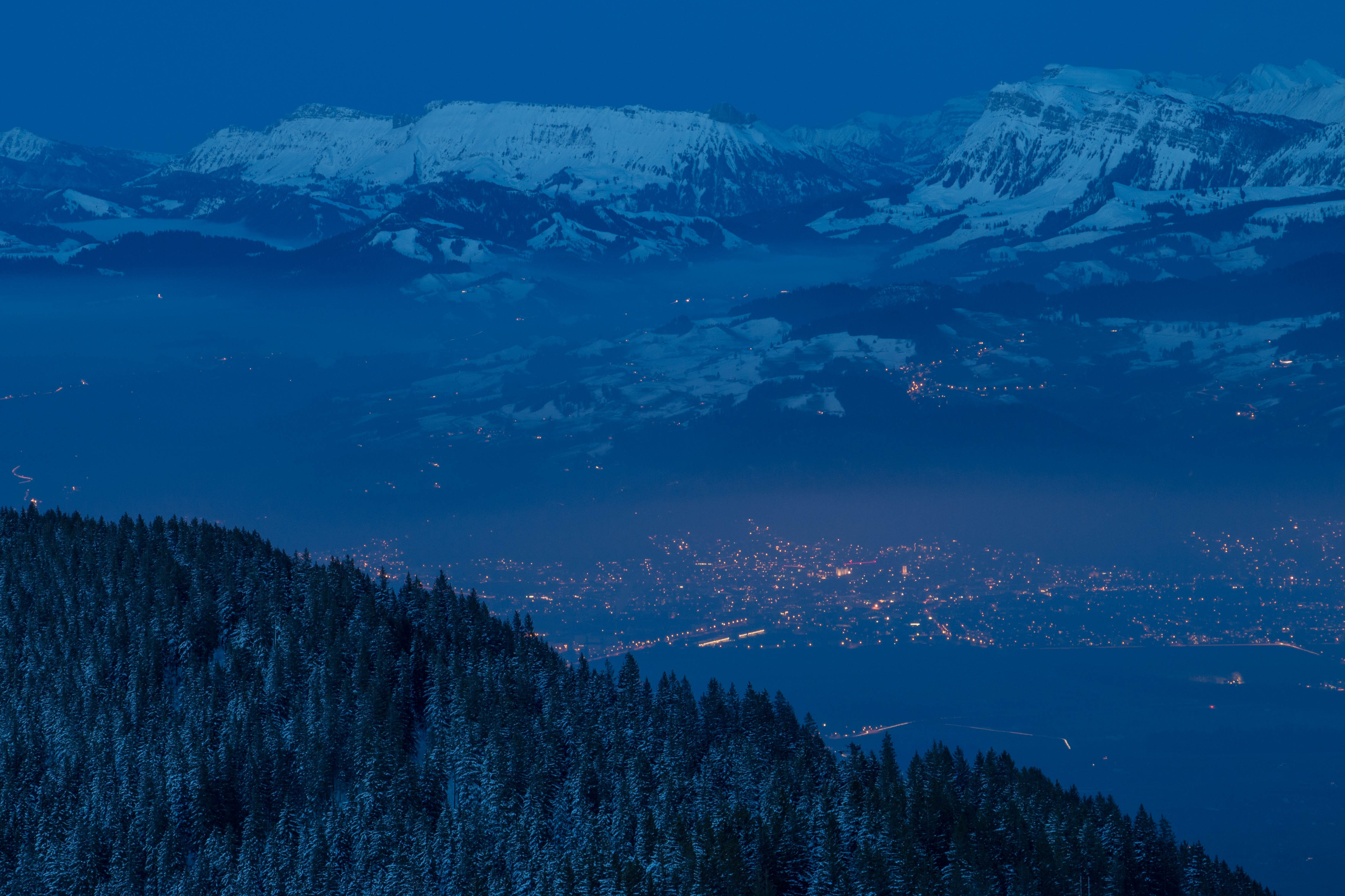 Forest slopes and snowy mountains overlooking the town of Thun on an inky blue night