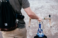 man holding brown and blue bicycle while walking outdoor during daytime