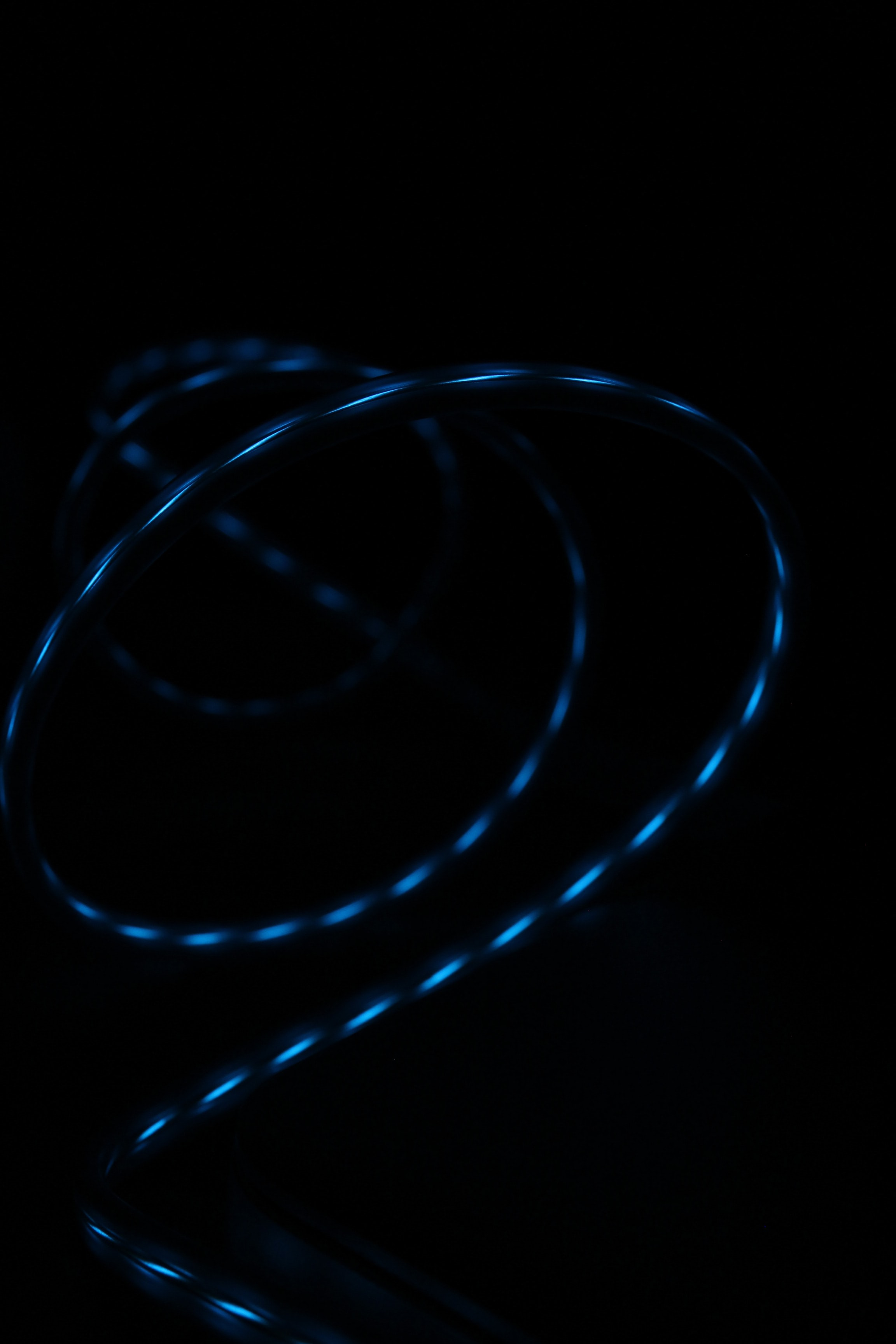 Blue light reflected in the glossy surface of a swirling wire