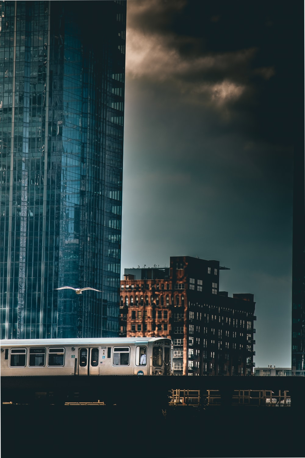 gray train passing by high-rise building