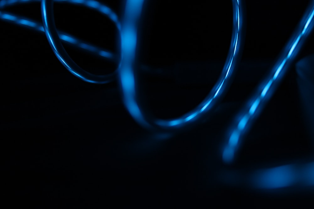 Blue light reflected in the surface of glossy swirling wires
