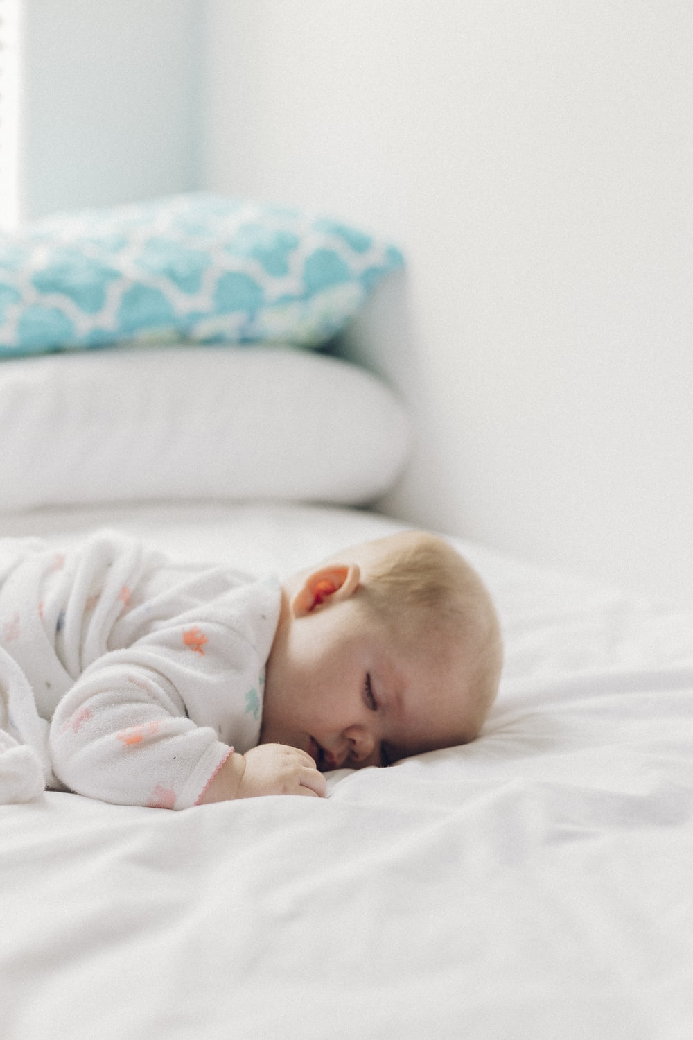 photo of baby laying on bed