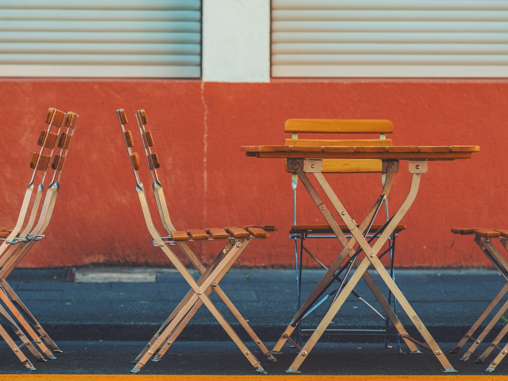 brown wooden table and chair near red wall