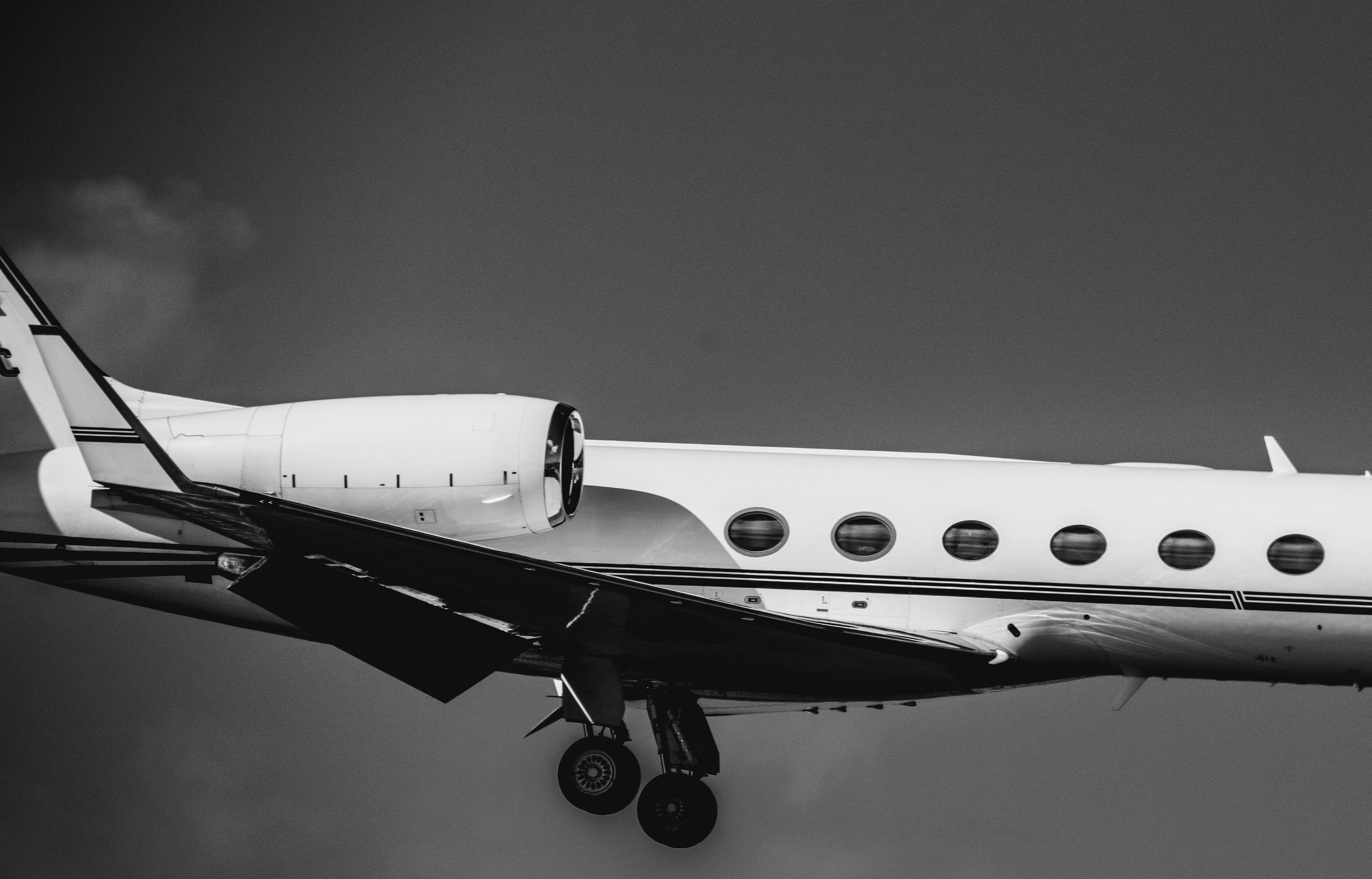 Cropped black and white photo of private jet in mid-flight.