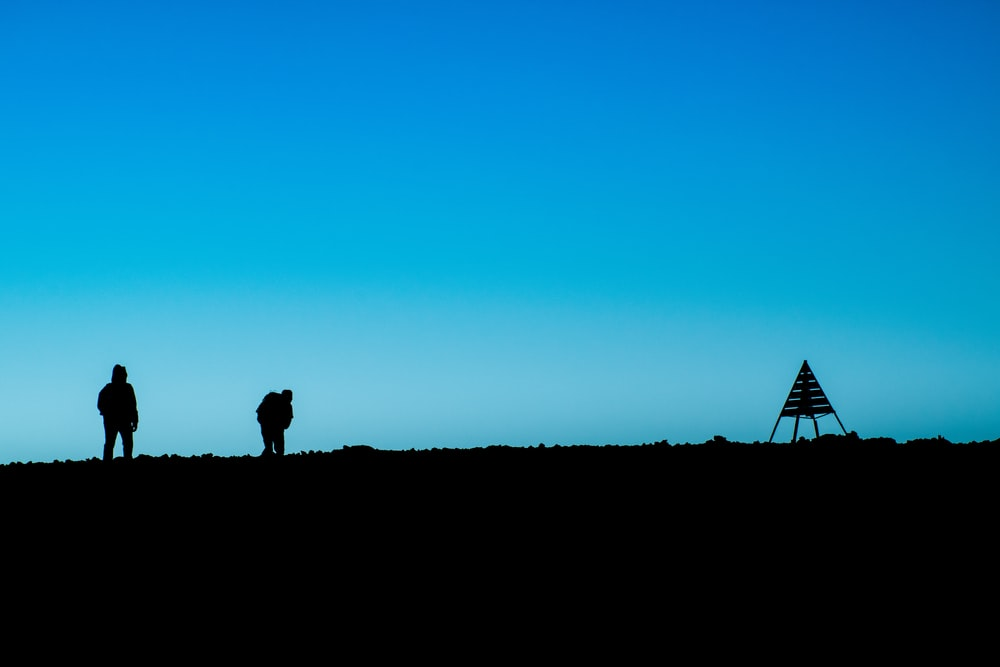 silhouette of two person standing on ground near tent at daytime