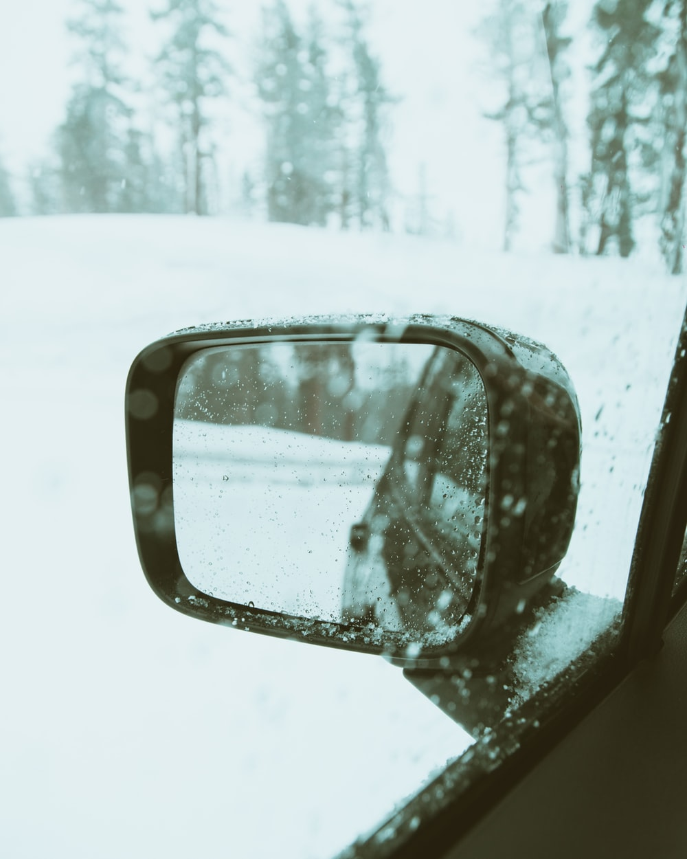 selective focus photography of left side mirror of vehicle on snow field