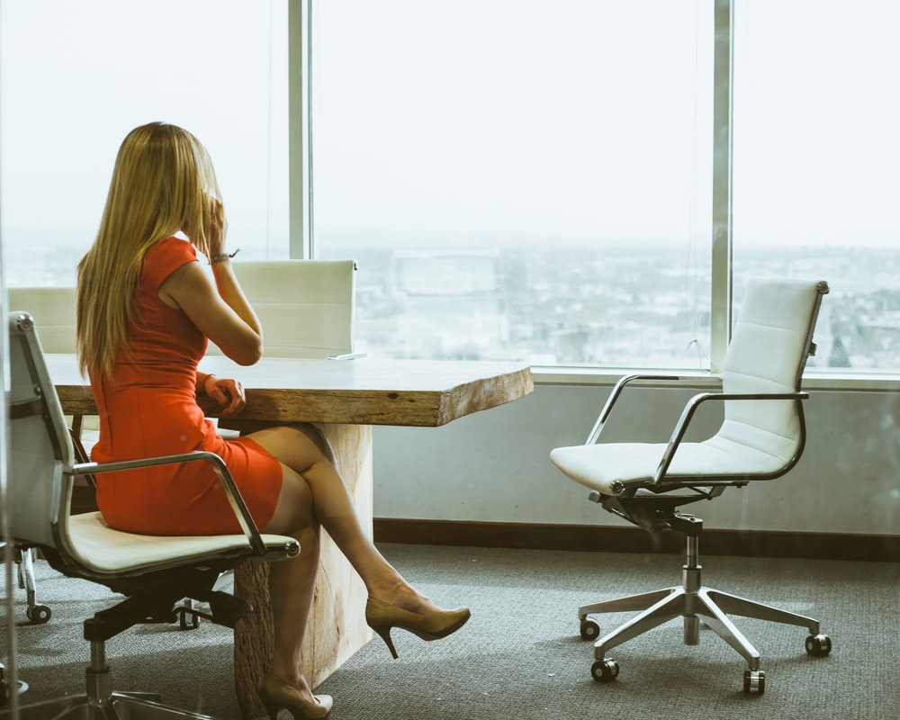 woman talking through mobile phone while sitting on swivel armchair