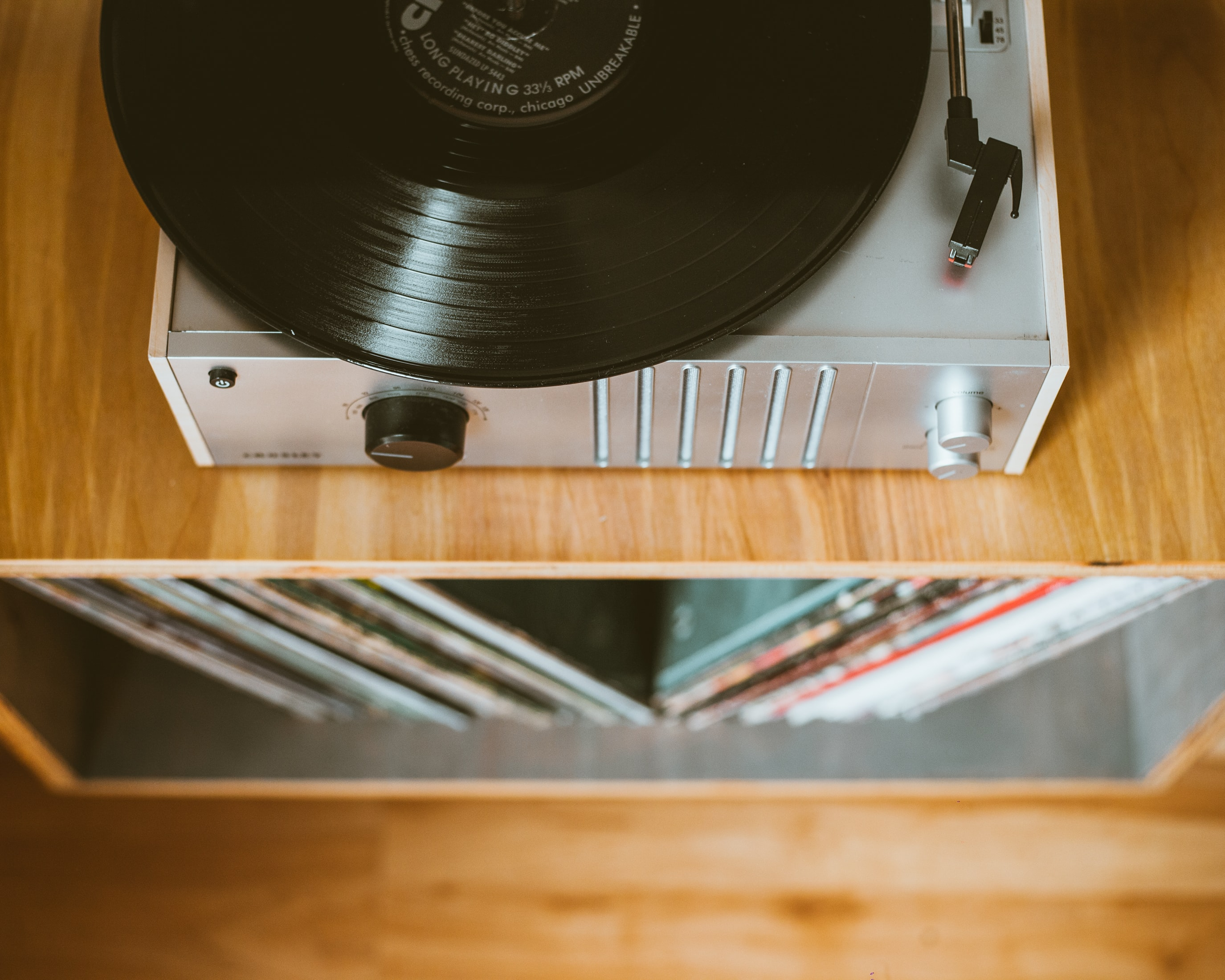 An overhead shot of a silver turntable on a wooden cabinet