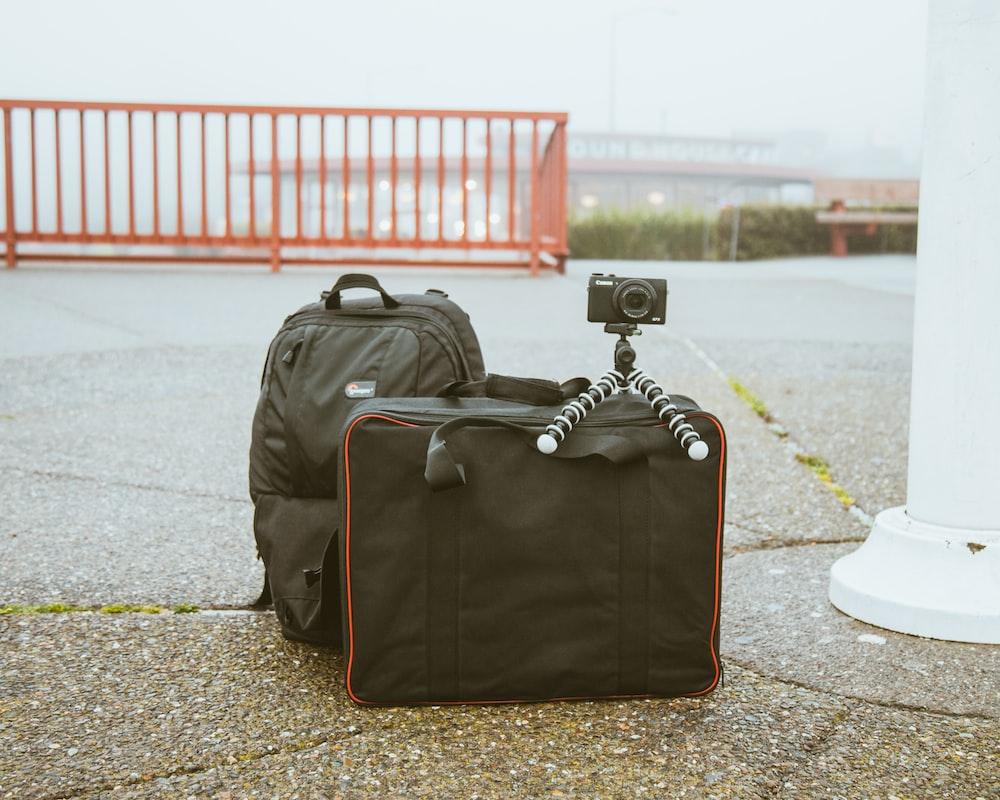 camera mounted on tripod on top of luggage bag