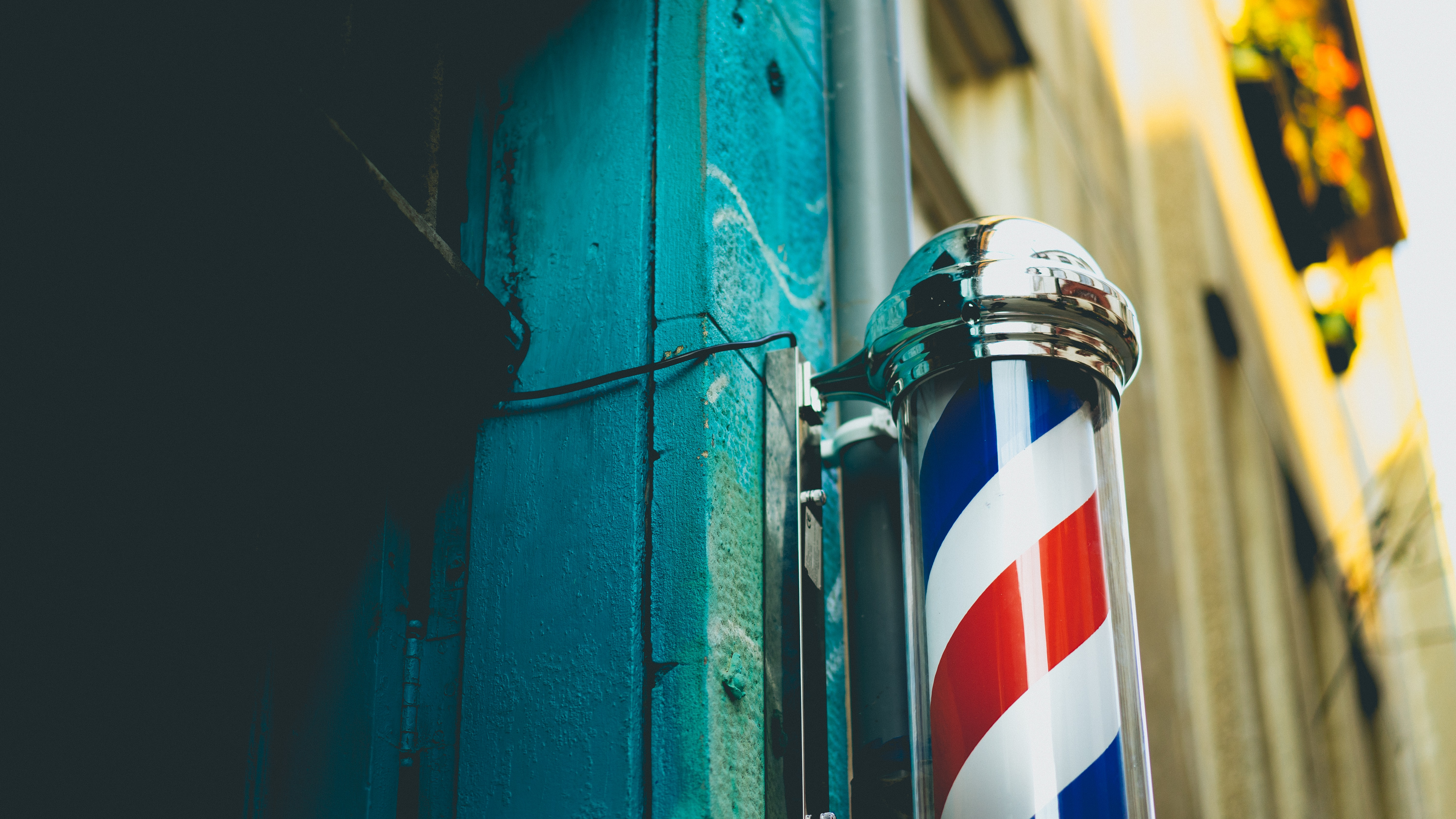 Barbershop red and white swirling pole capped by steel ends beside an aquamarine wall