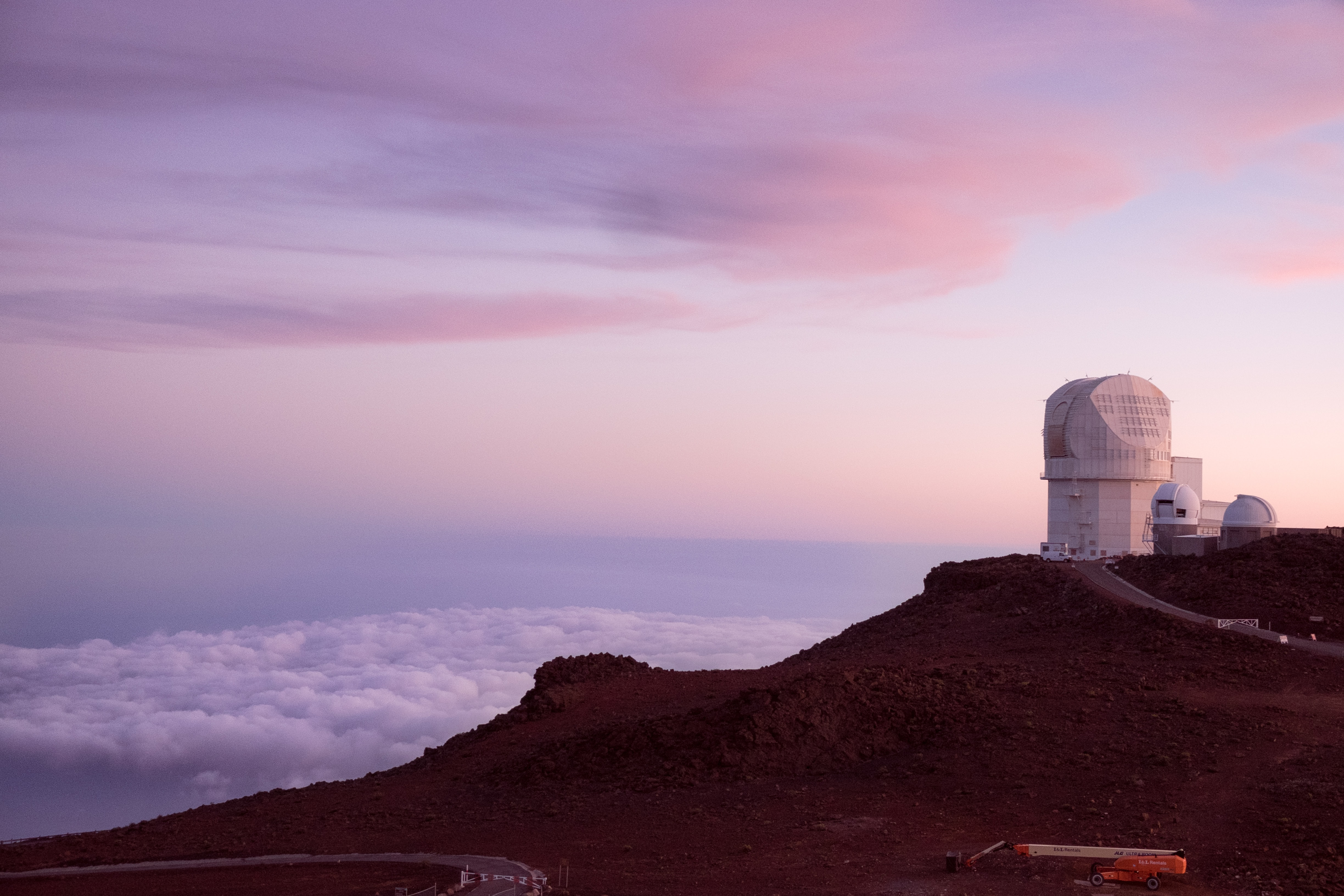 Observatory above the clouds atop Haleakala Crater, Maui during a pastel sunset