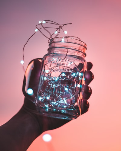 person holding clear glass mason jar with strip lights inside