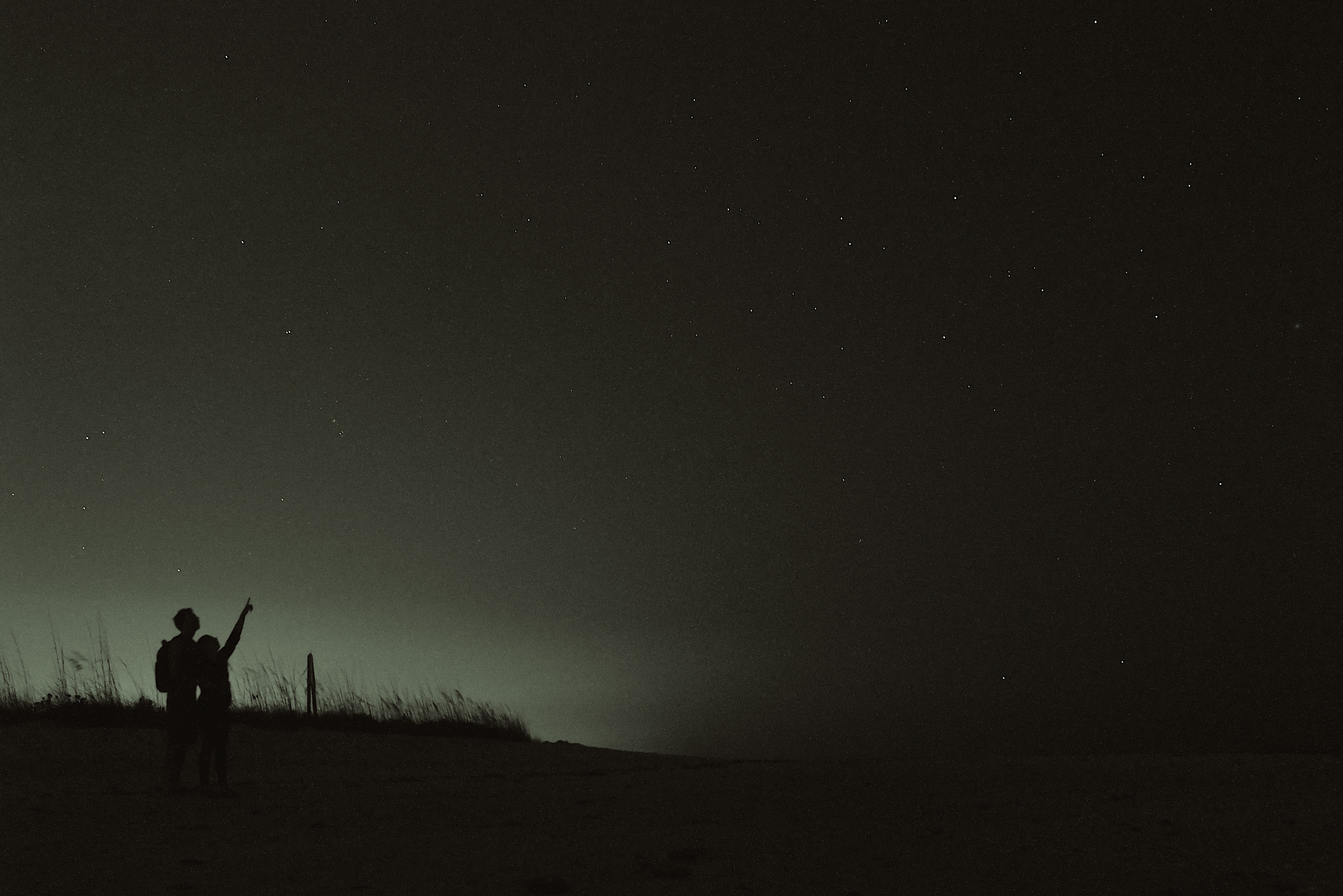 Couple looking up towards black night sky, one with arms outstretched