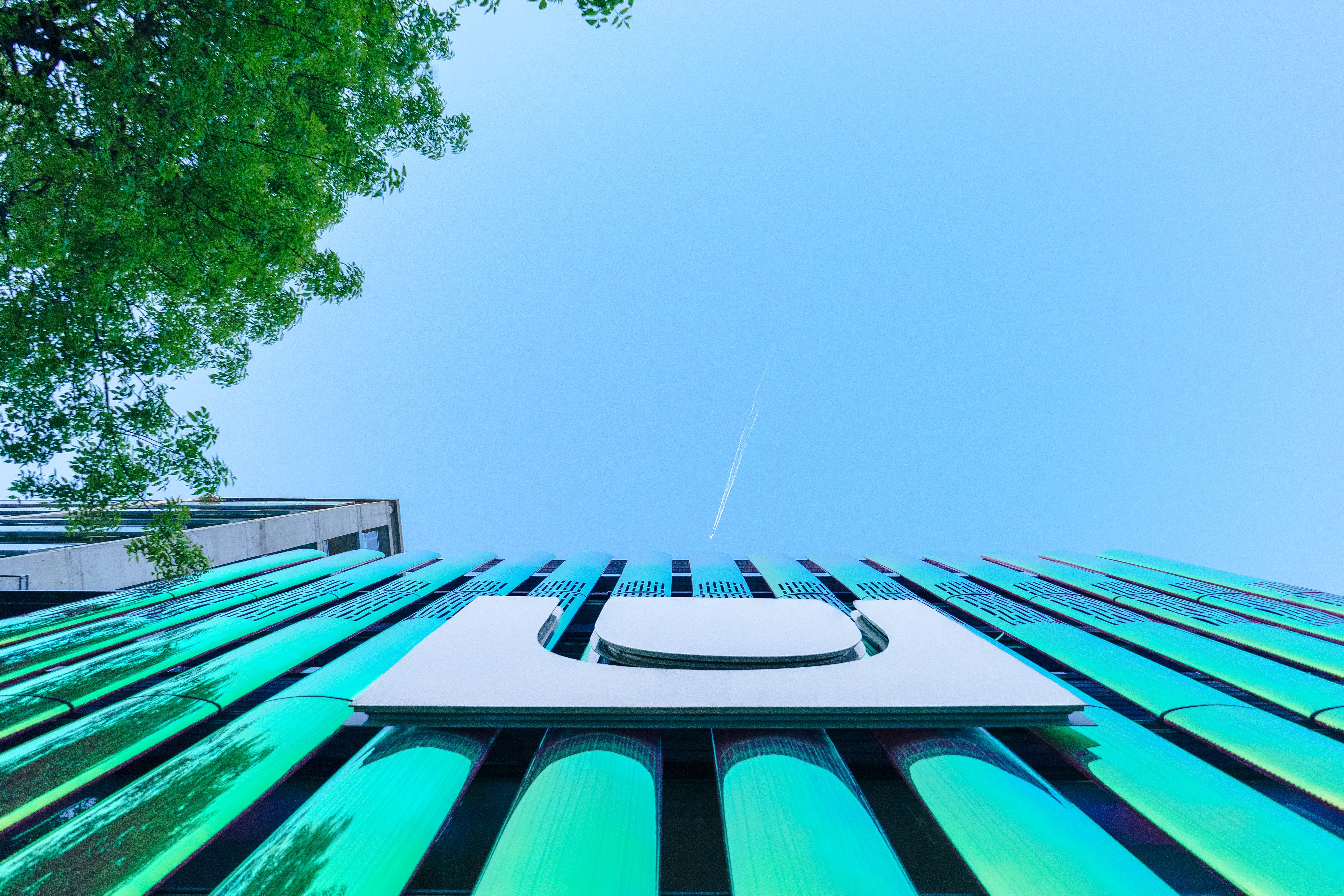 low angle photography of building under contrail