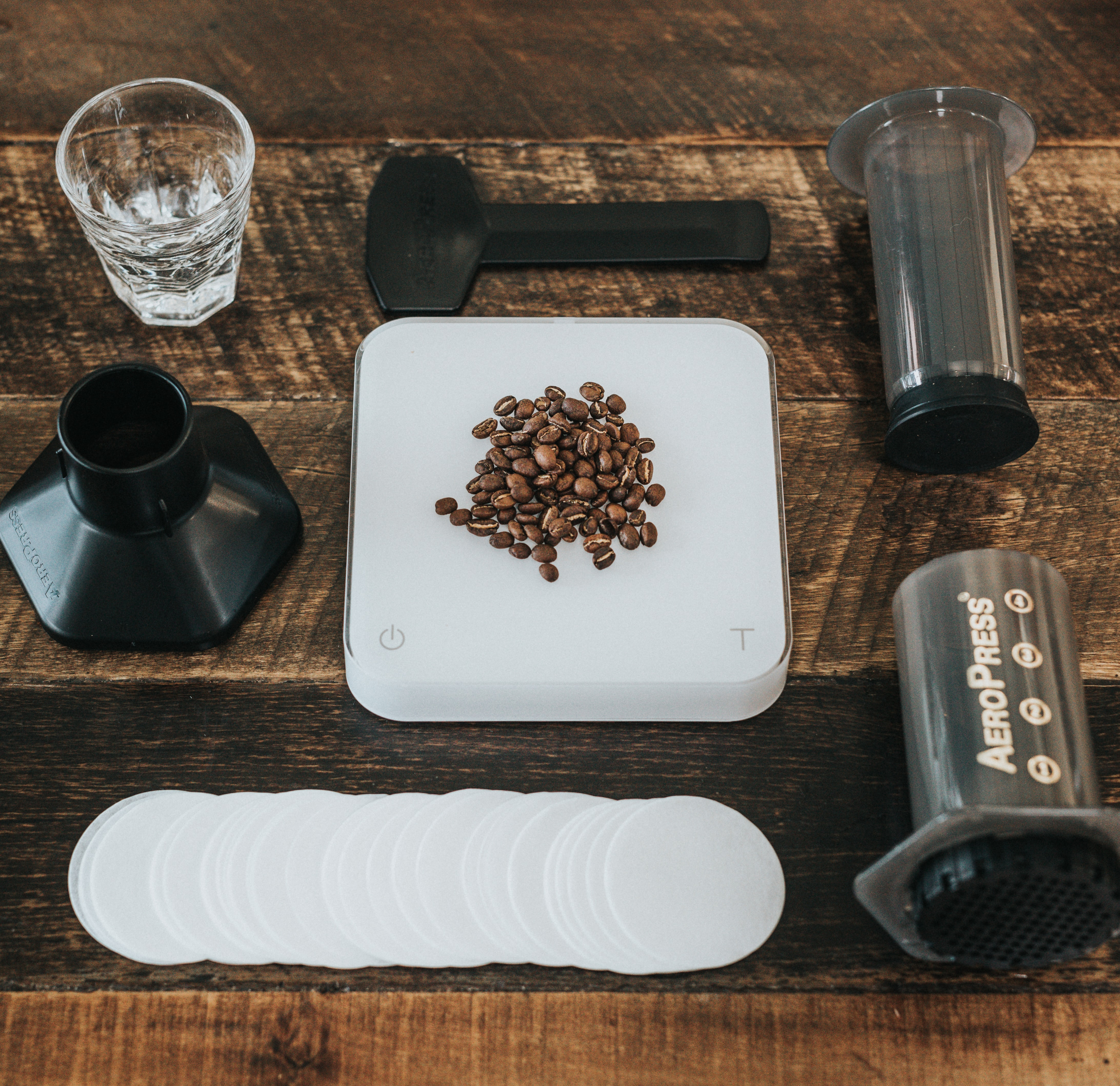 Aeropress coffee press kit disassembled on a wooden table with coffee beans in the center