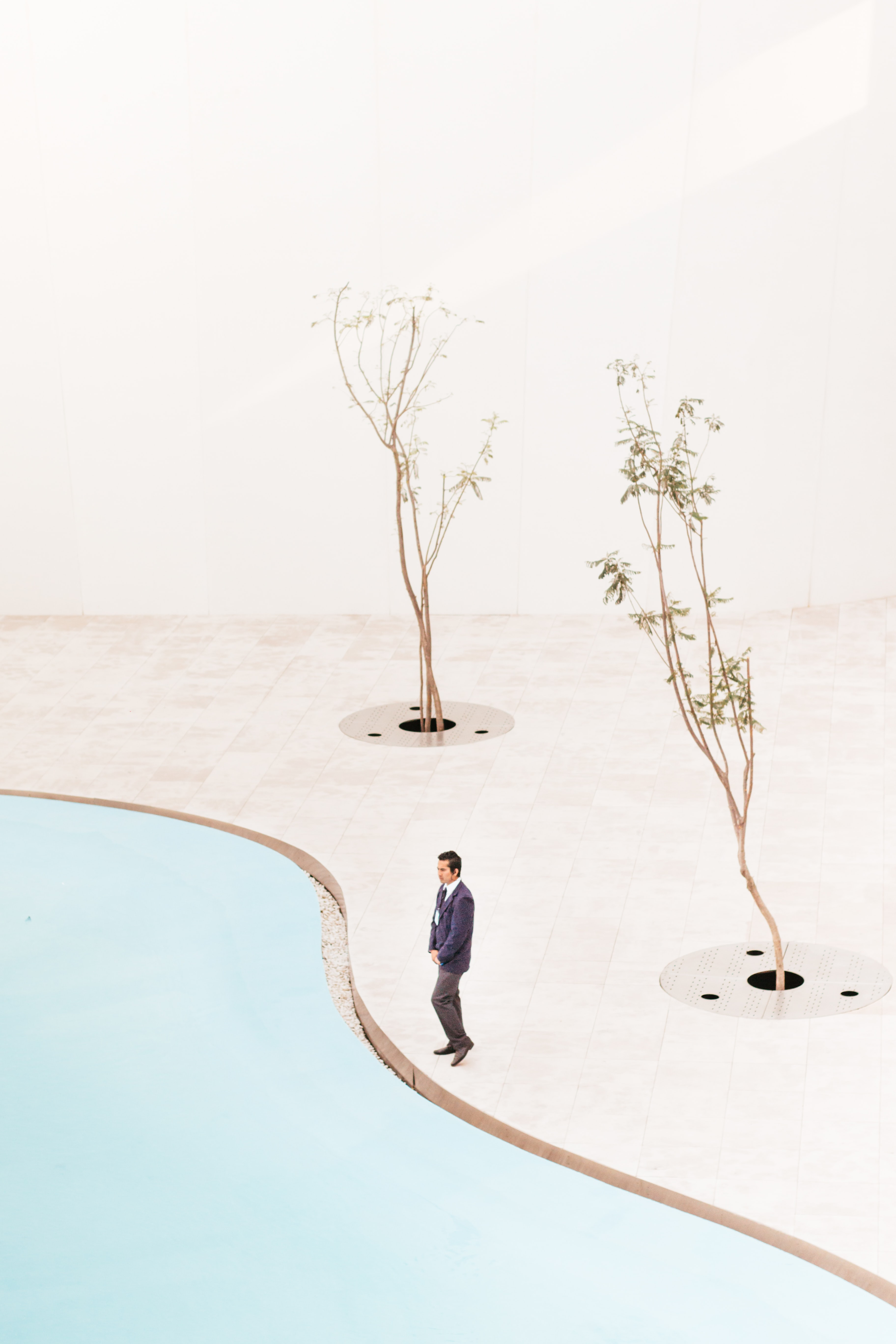 A man in a suit standing at the edge of a pool