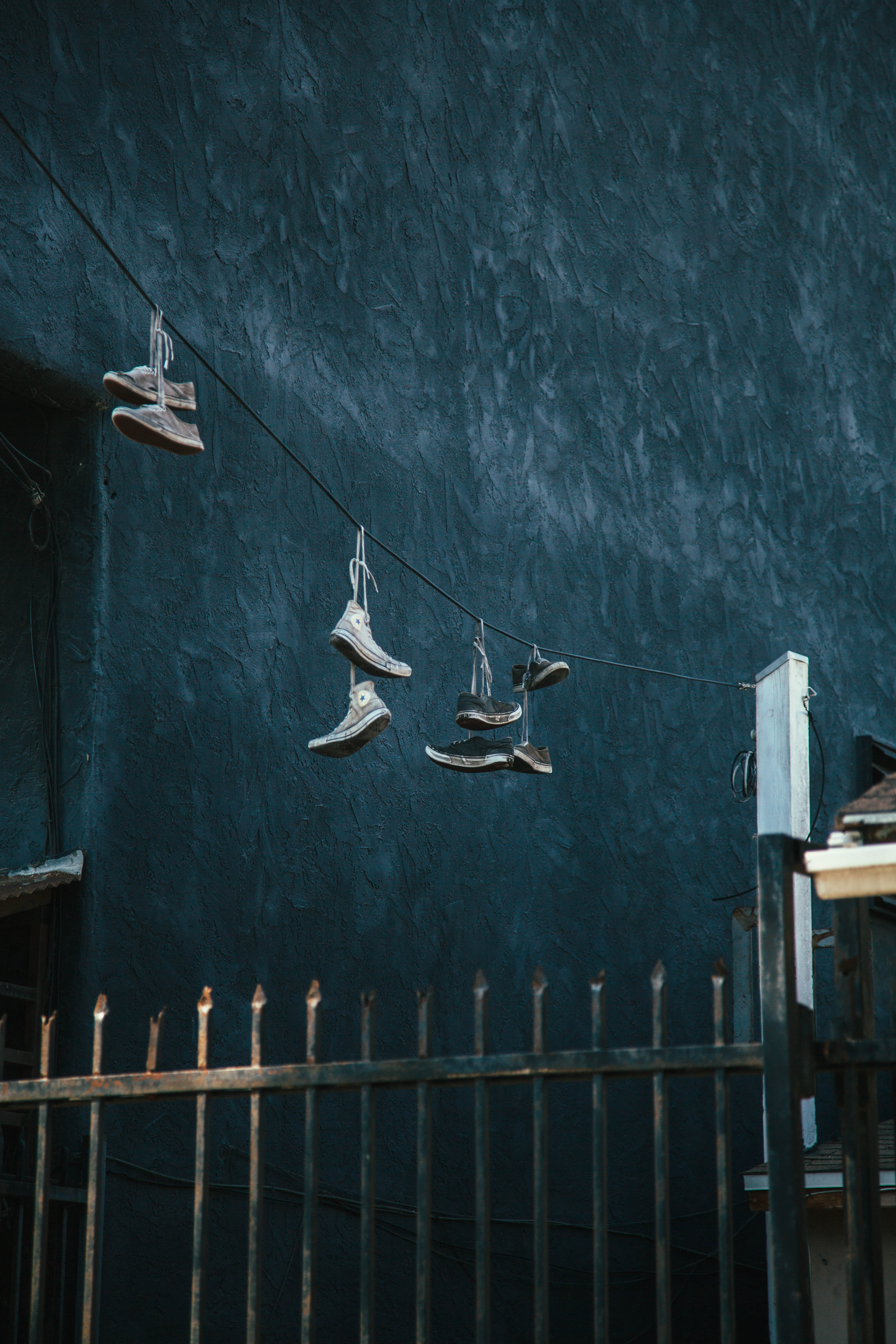 shoes hanged on black wire near metal gate