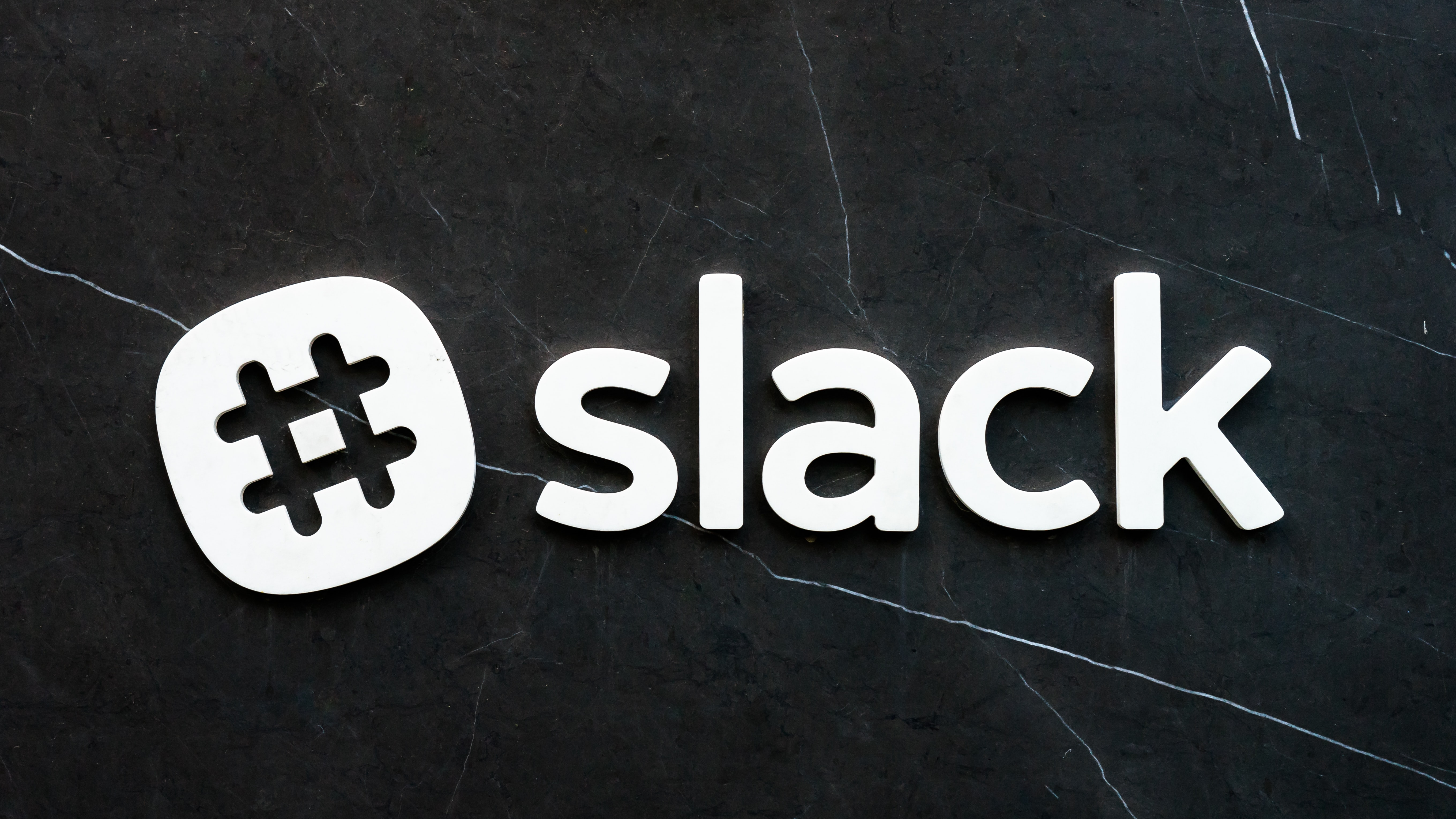 Slack company logo on a black marble wall