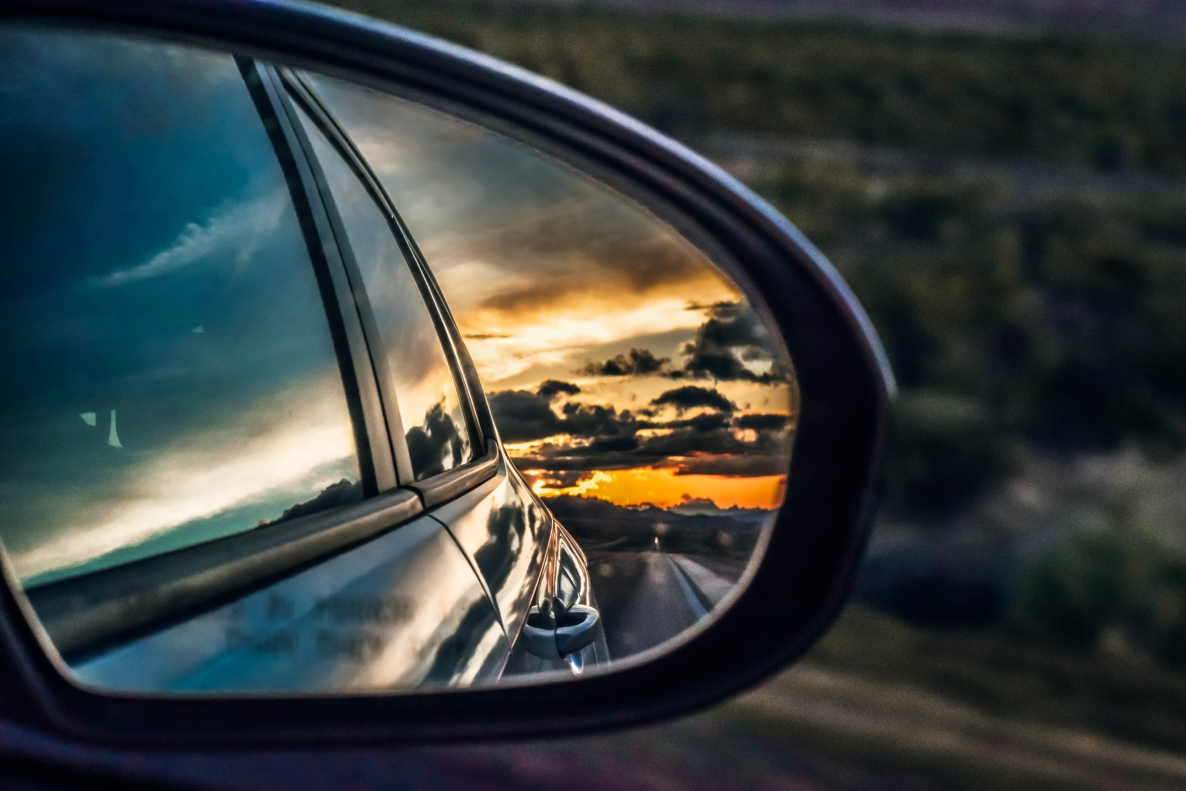 View of the sunset and the clouds from the car on the side view mirror