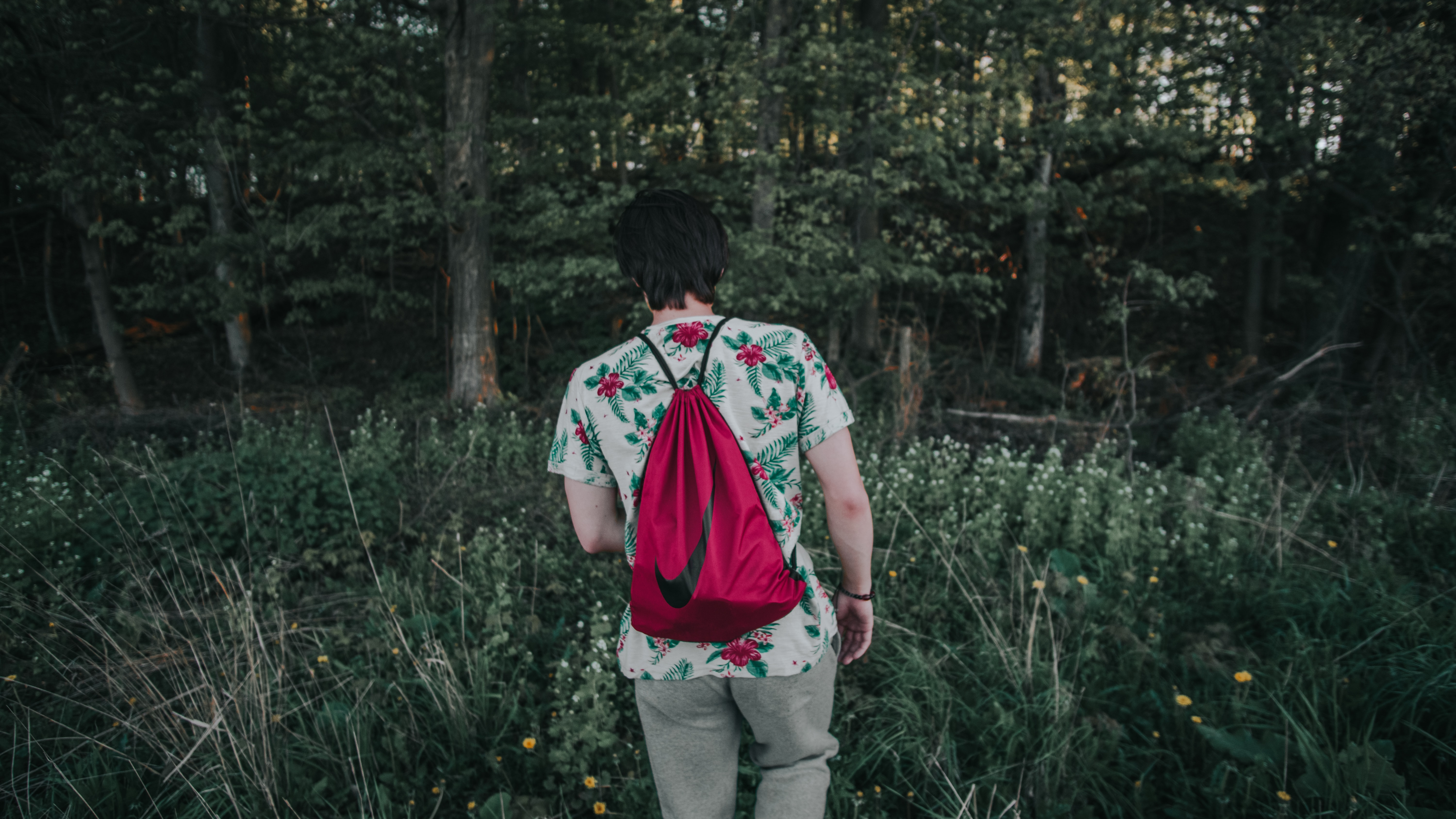 A person with a red back on their back standing back to camera in a forest