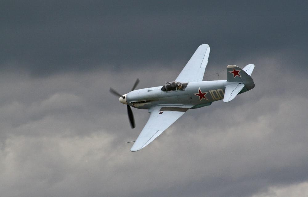 gray bi-plane under gray clouds