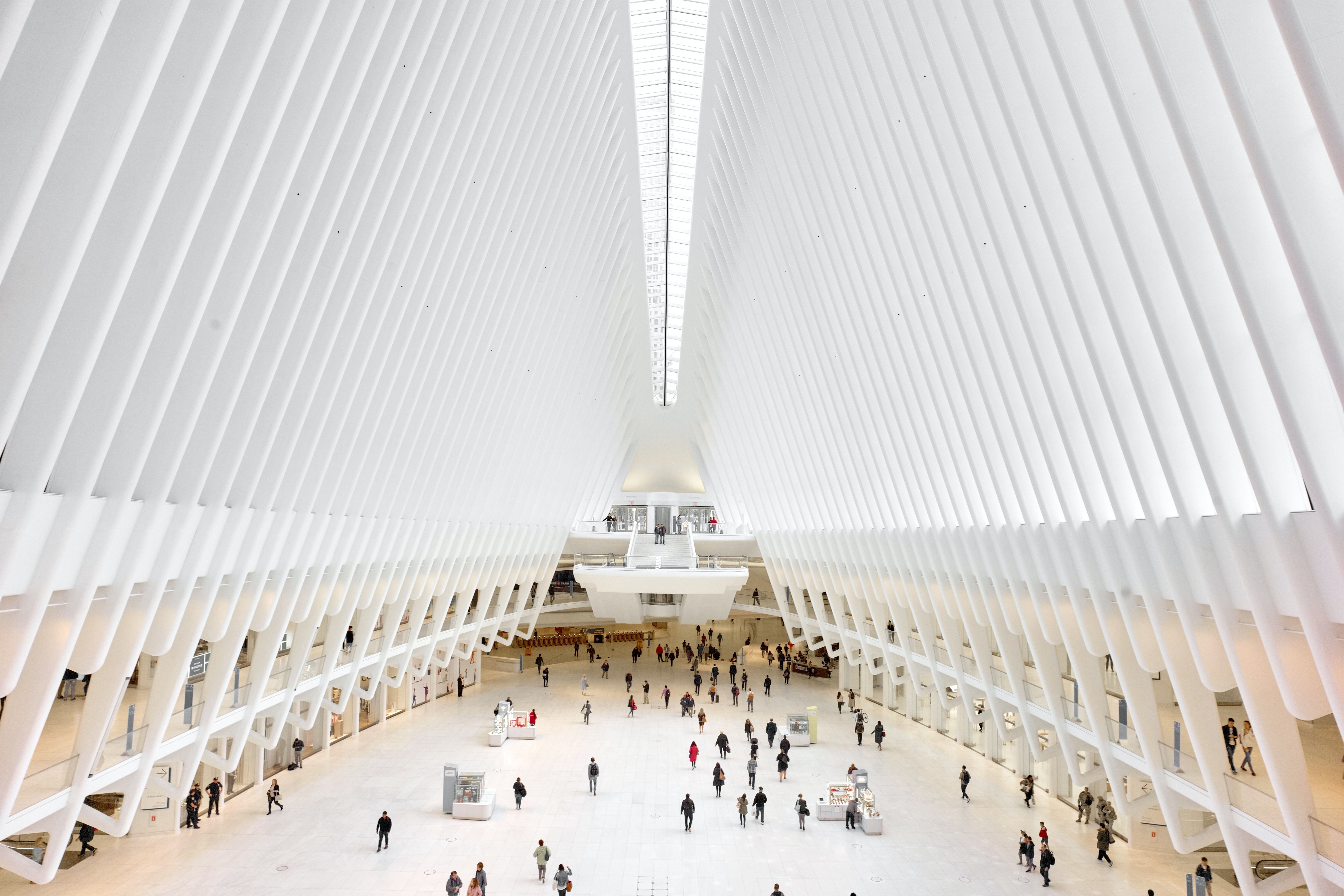 Commuters in the modern white interior of the World Trade Center terminal station