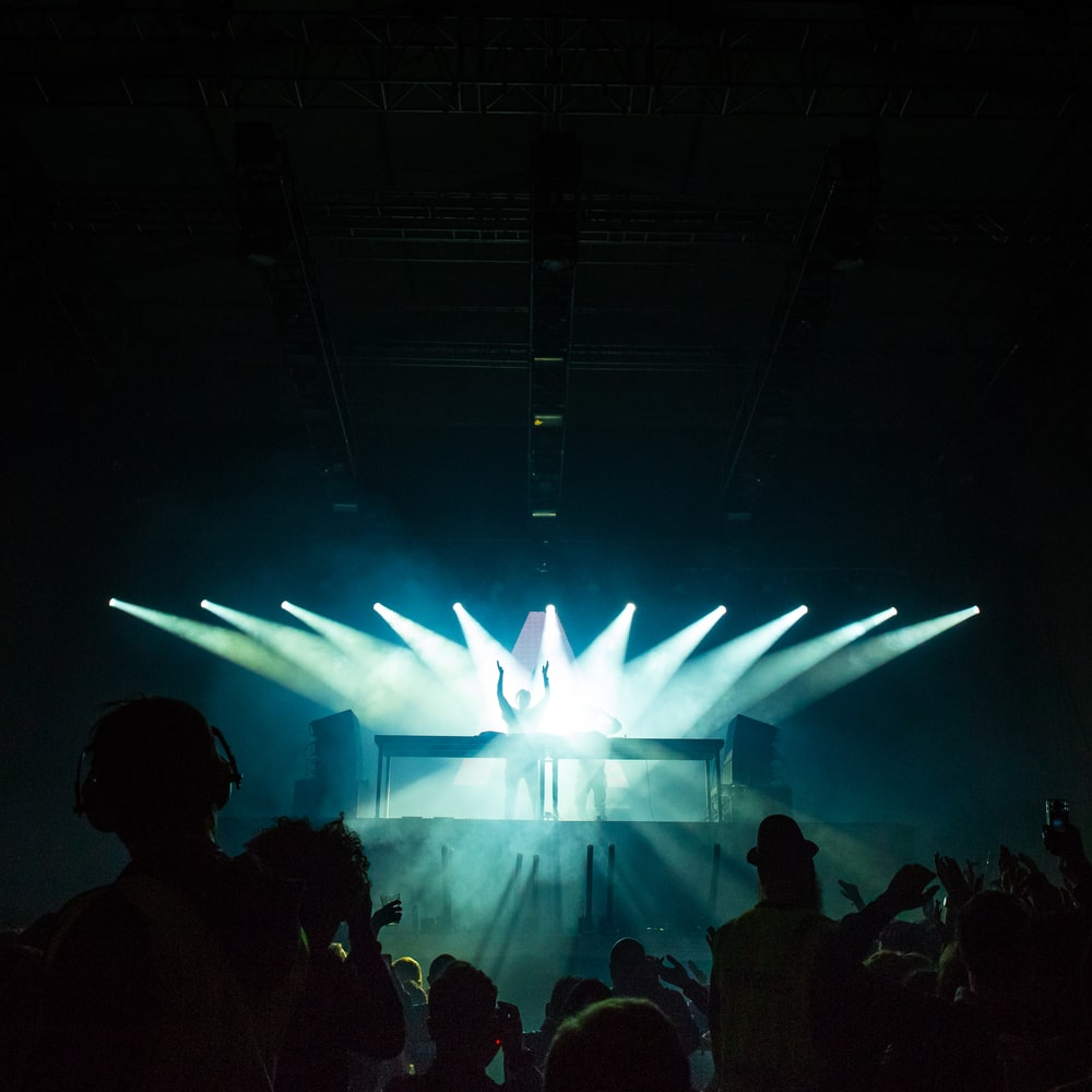 person standing under stage lights facing crowd