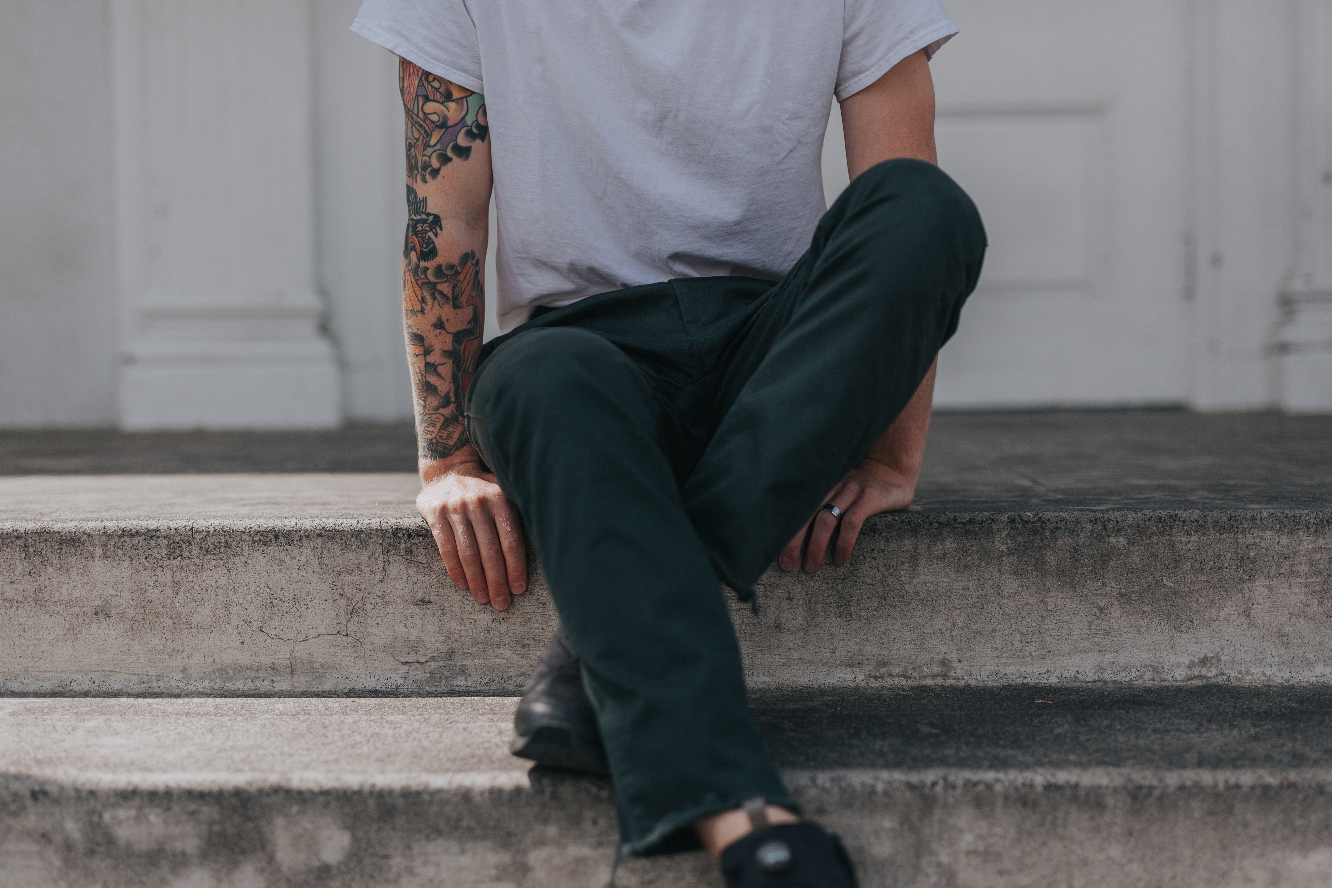 Low shot of a person with an art tattoo sitting on a porch step
