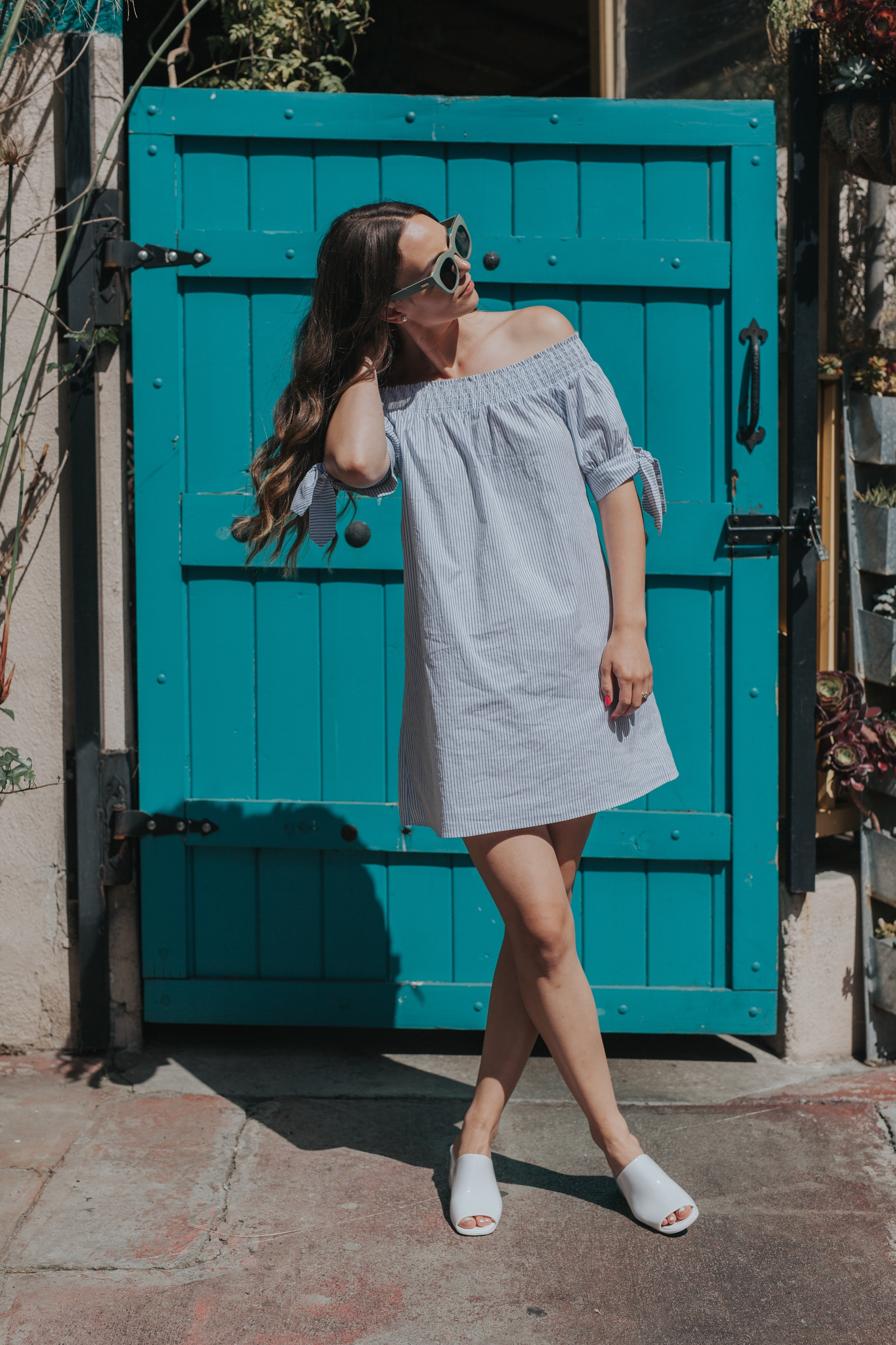 A young woman in sunglasses and a dress in front of blue wooden door