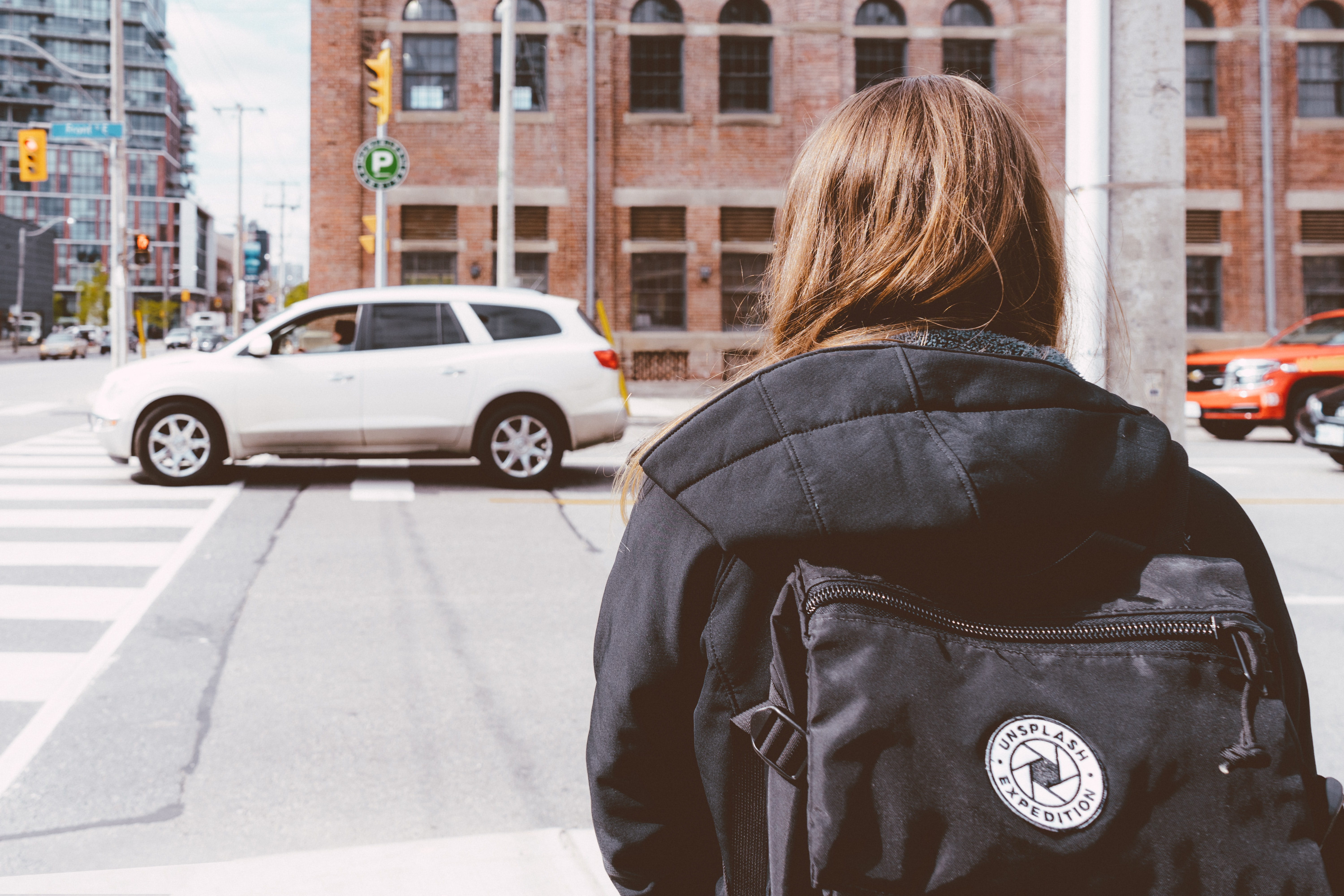 A woman with a black backpack waiting to cross the street in Toronto