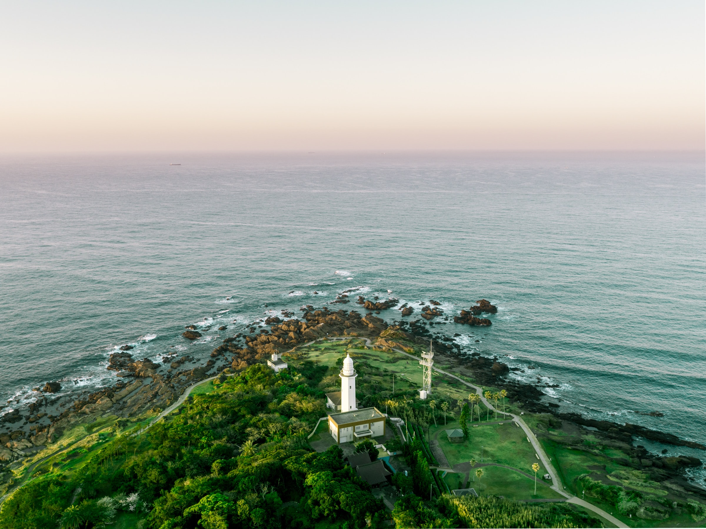 aerial photography of white tower on island near sea under white clouds