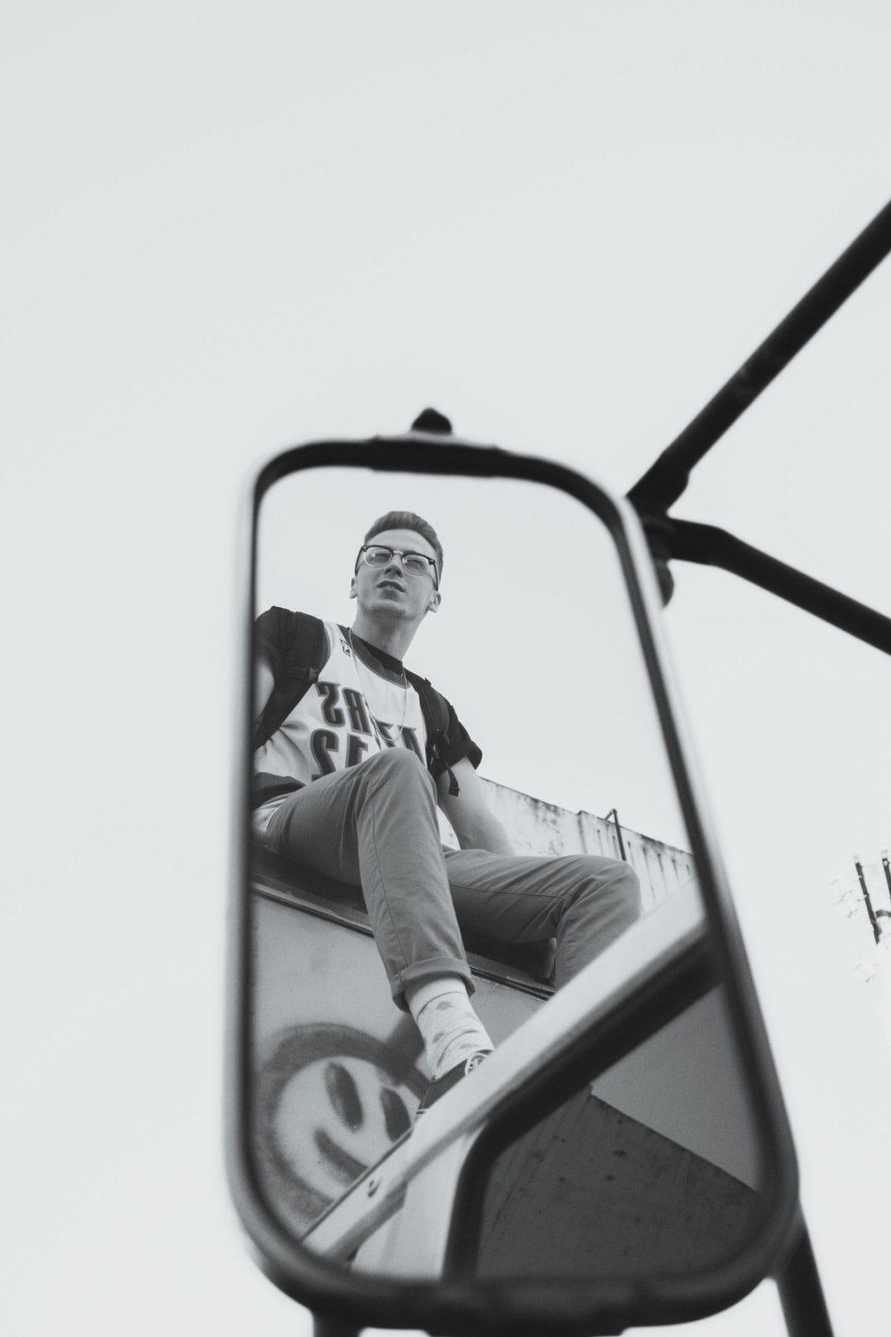 grayscaled photo of reflection of man in side mirror