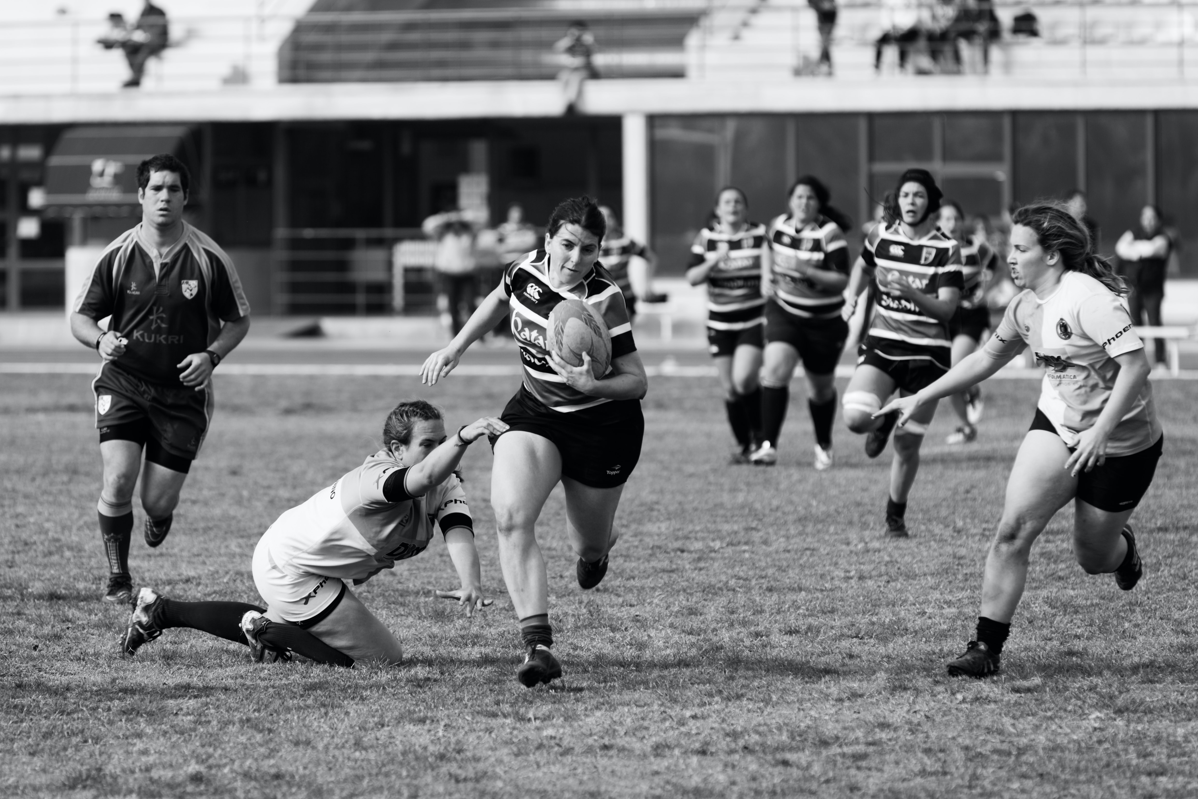 grayscale photo of women playing rugby football