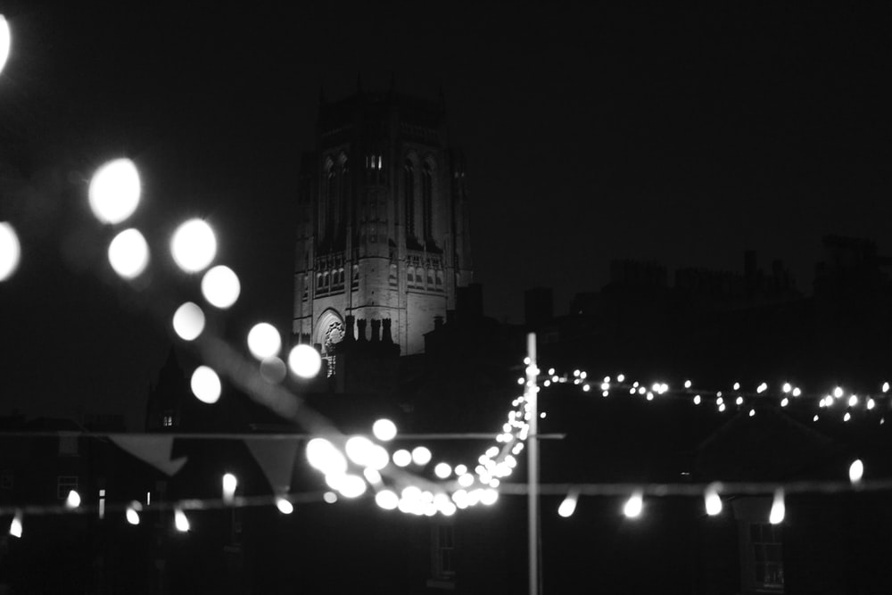 grayscale photography of stringlights and tower