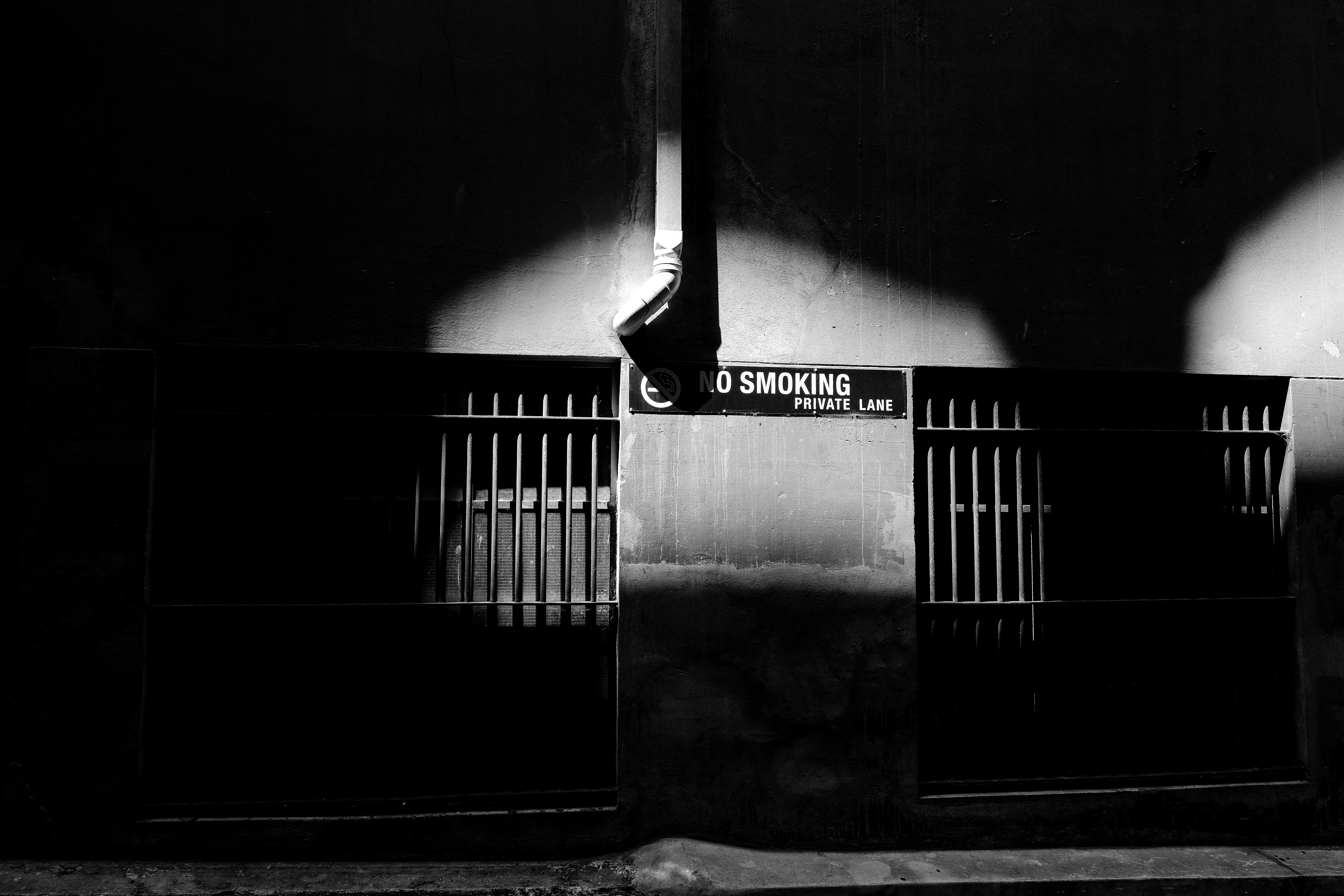 A No Smoking sign is seen on a wall in a dark alley in Melbourne.