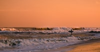 Surfer standing in shallow water, looking at waves at sunset in Bradley Beach