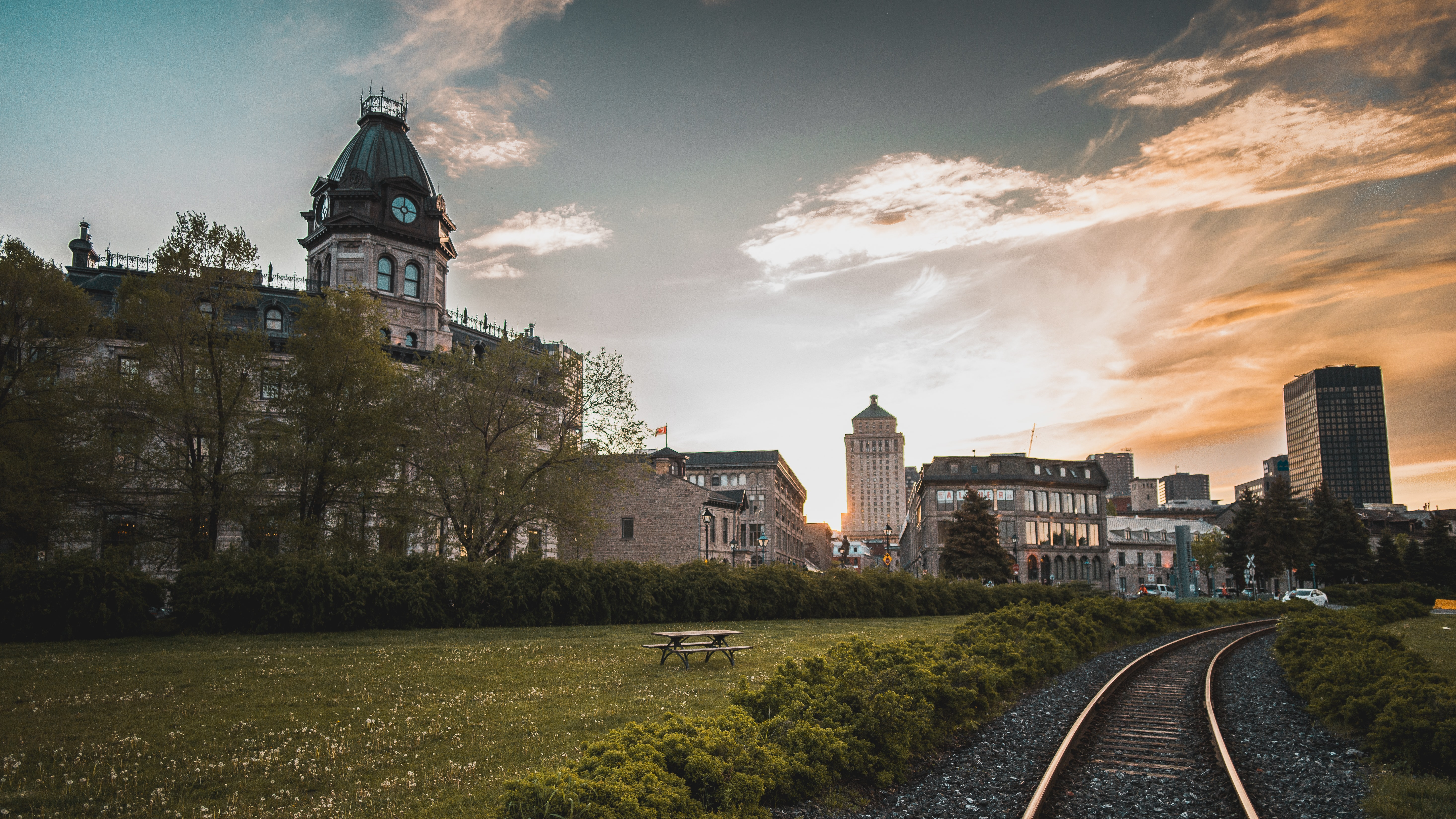 train rail near concrete houses during daytime