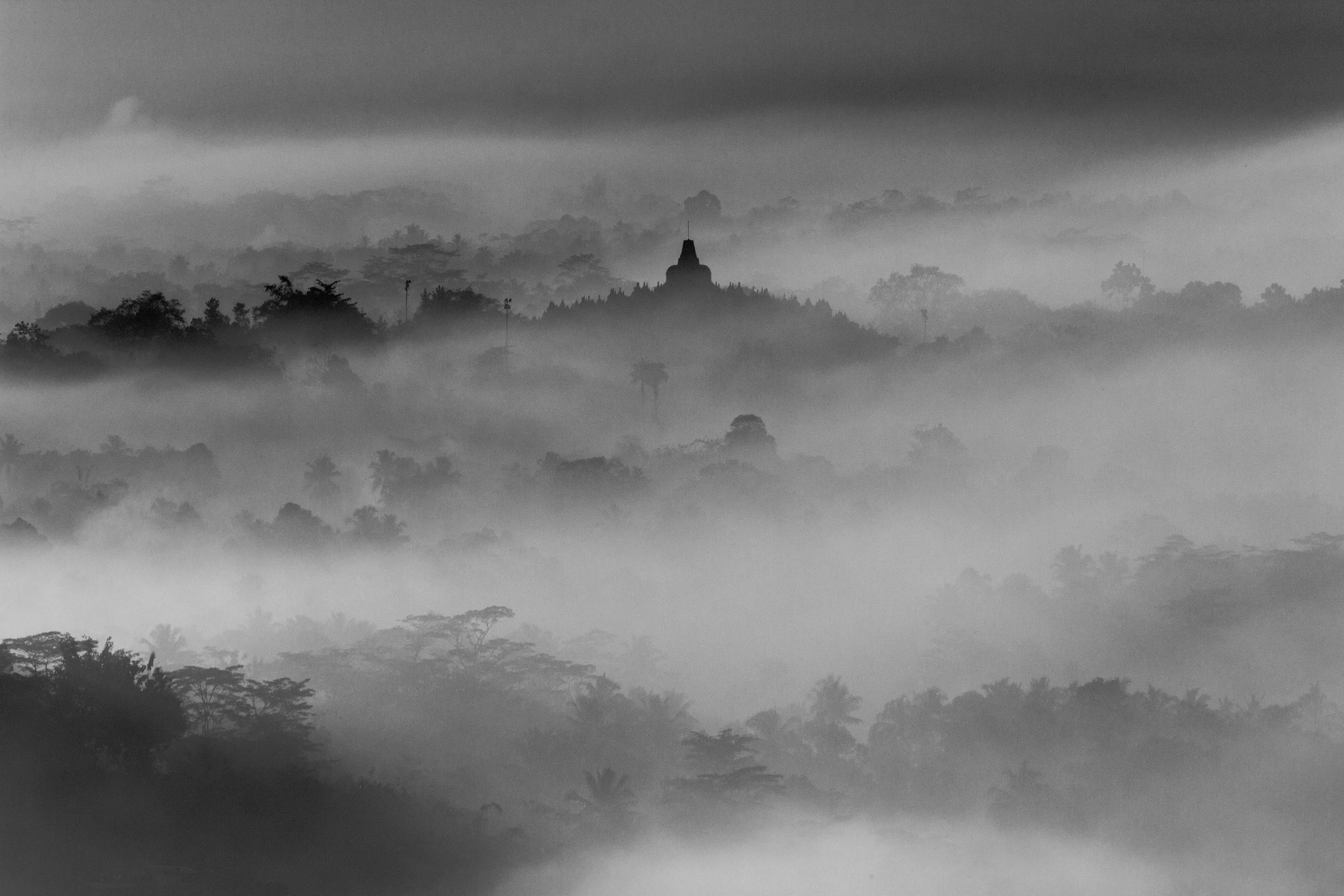 A desaturated shot of the silhouettes of wooded hills with a spire of a temple rising up above the mist