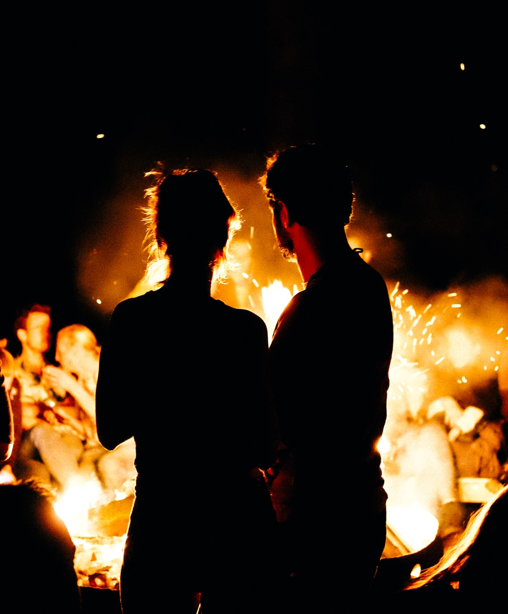 two persons standing in front of bonfire