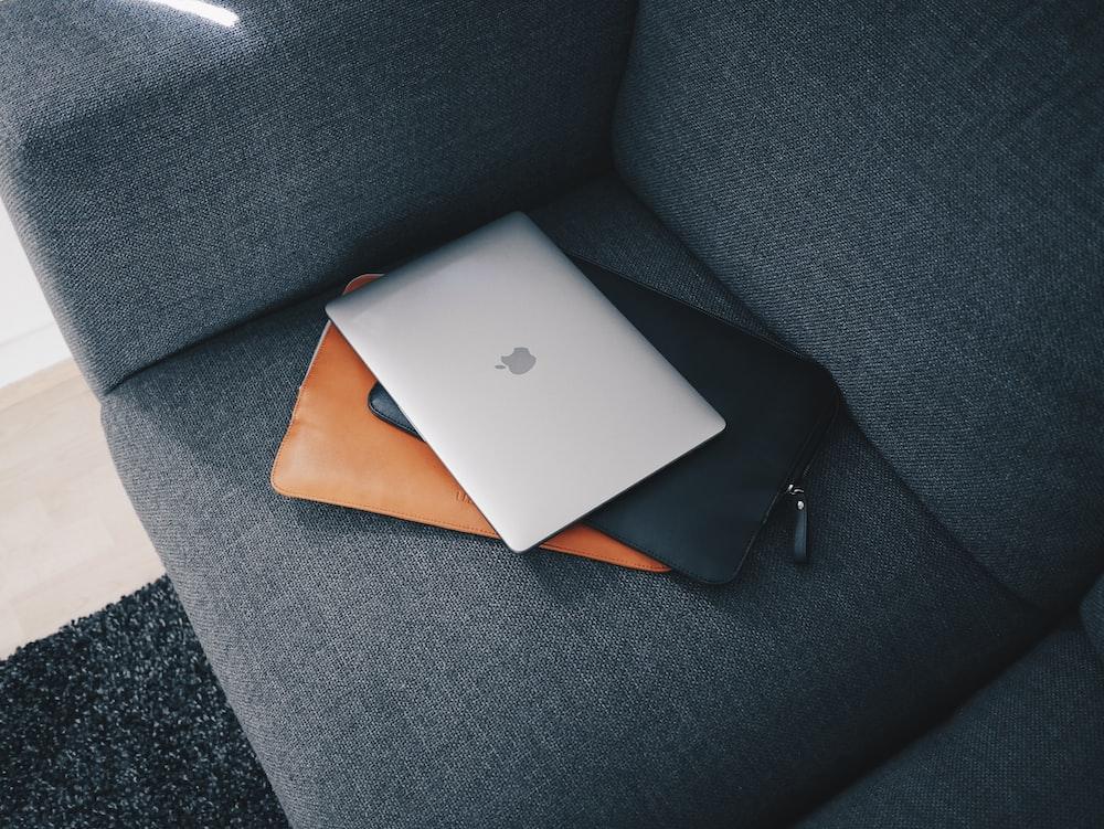 silver macbook on gray sofa