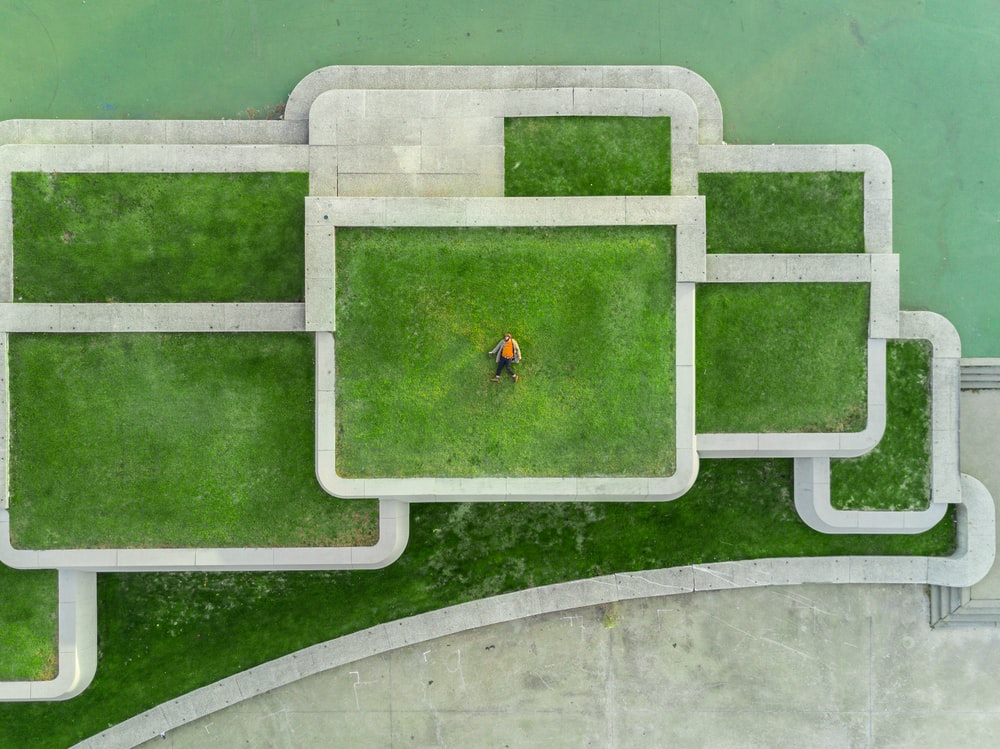 bird's eyeview photo of person lying on green grass