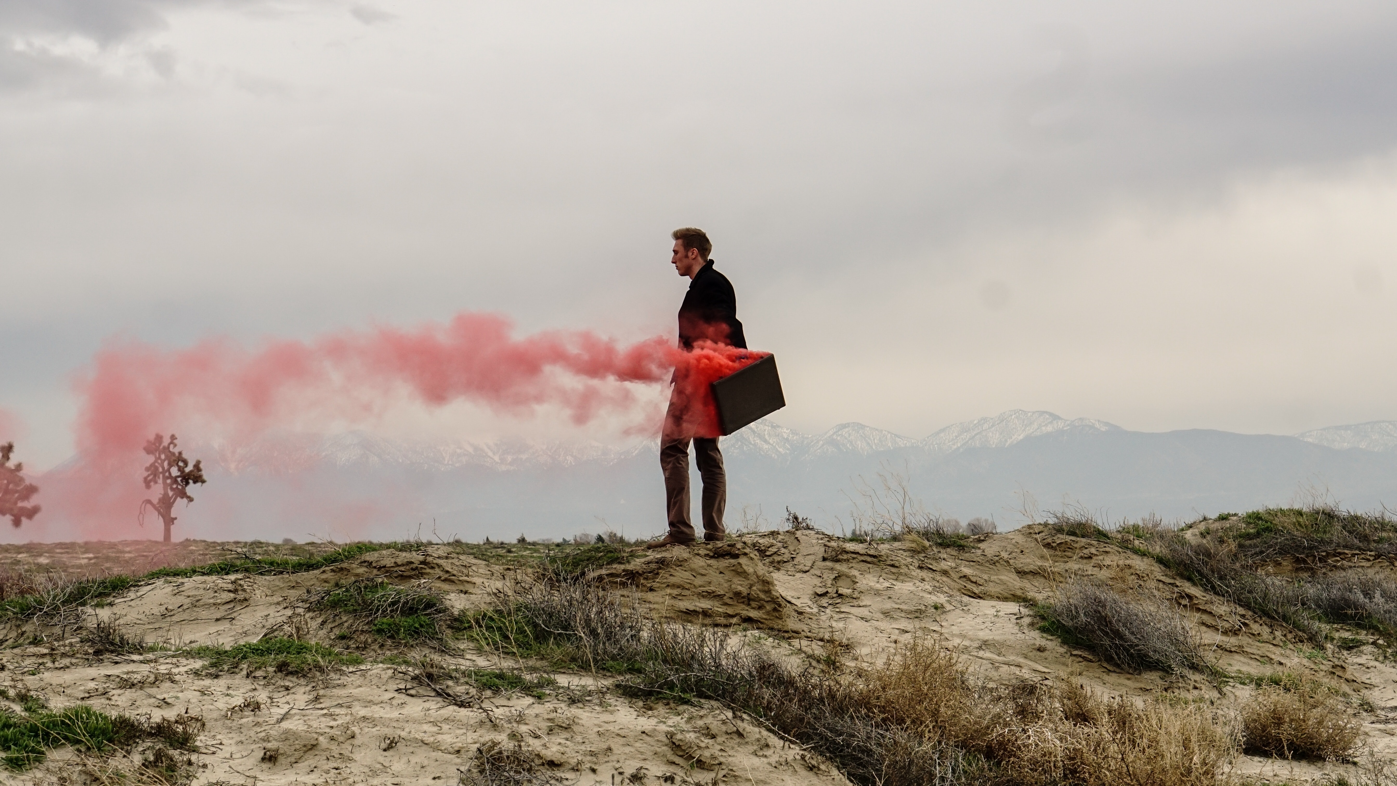 Red smoke coming out of a man's briefcase.