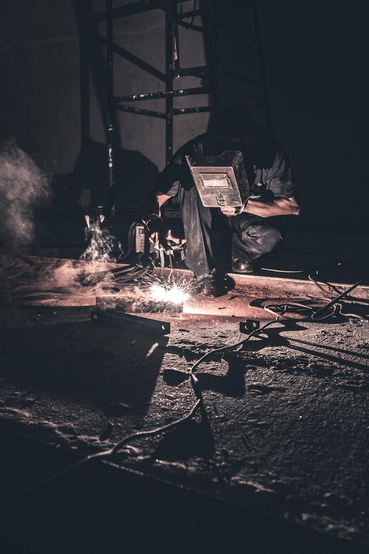 man welding black metal